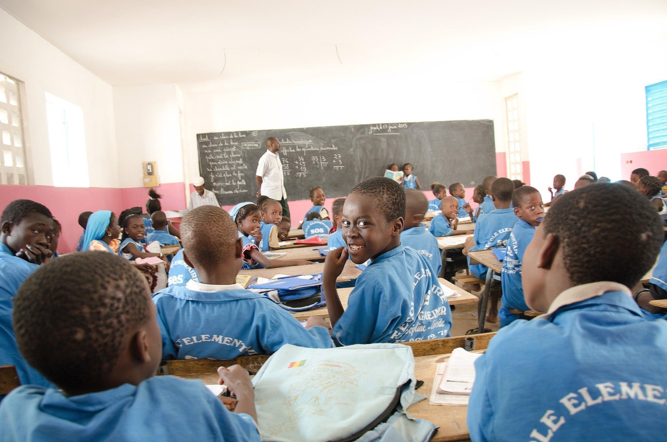 Eines von vielen Schulkindern in der Schule dreht sich lachend nach hinten um.