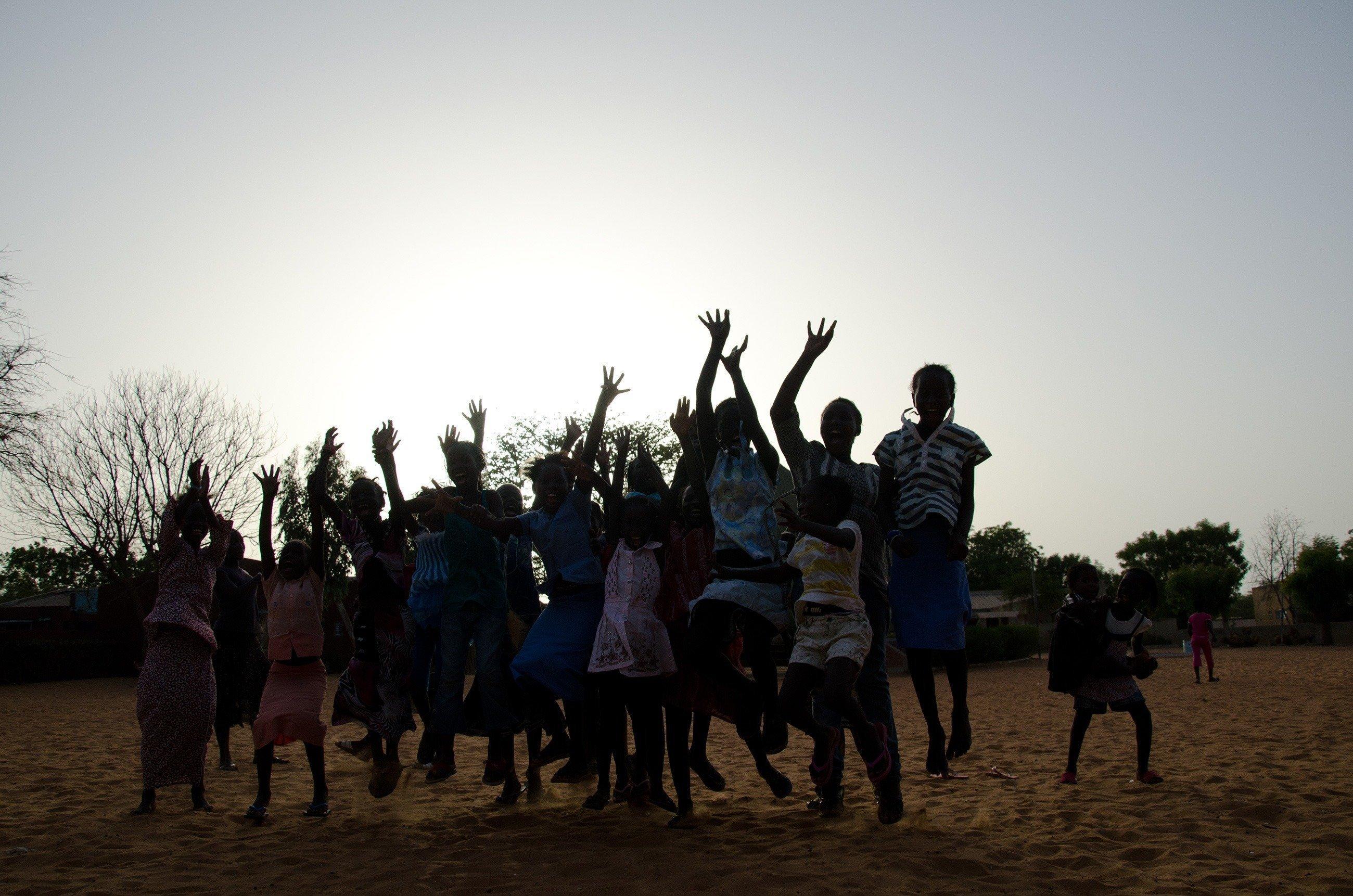 Eine Gruppe von Kindern springt vor einem Sonnenuntergang hoch.