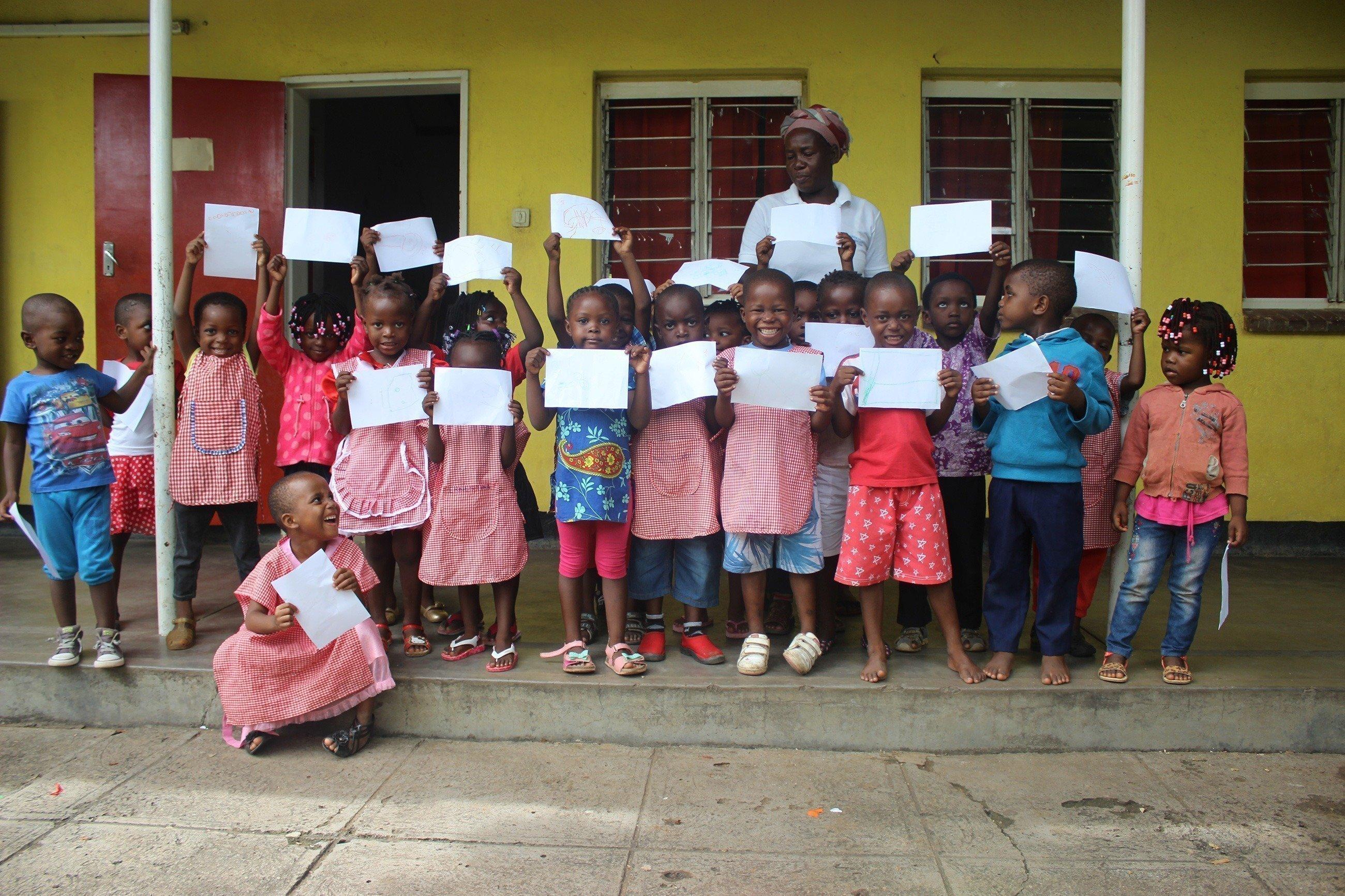 Un groupe d'enfants devant une maison et tenant des images dans leurs mains.