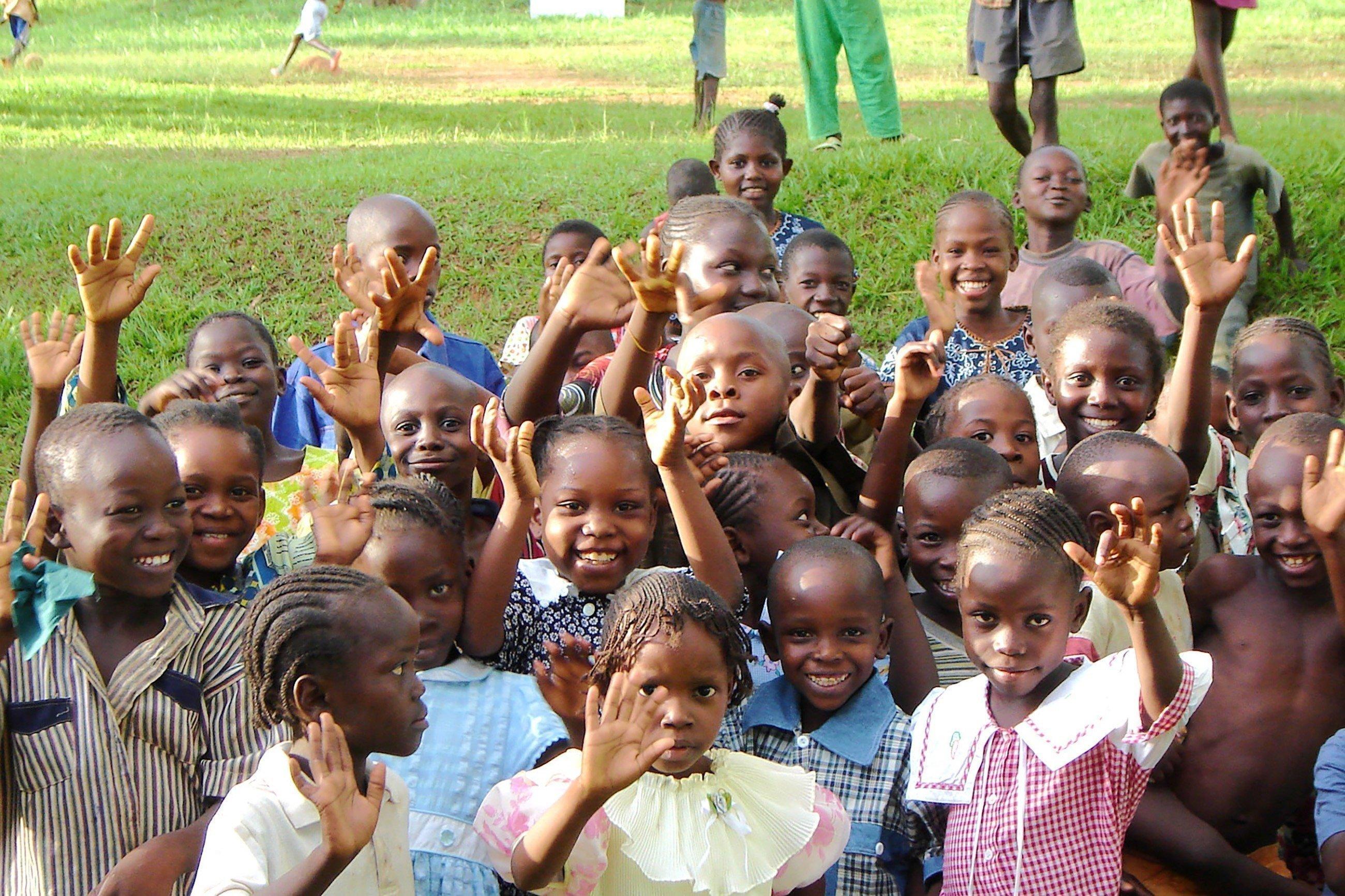 Des enfants faisant un signe de la main en riant.