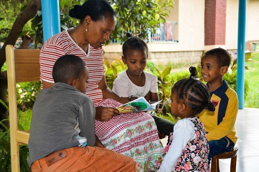 Une mère lisant quelque chose à ses enfants.