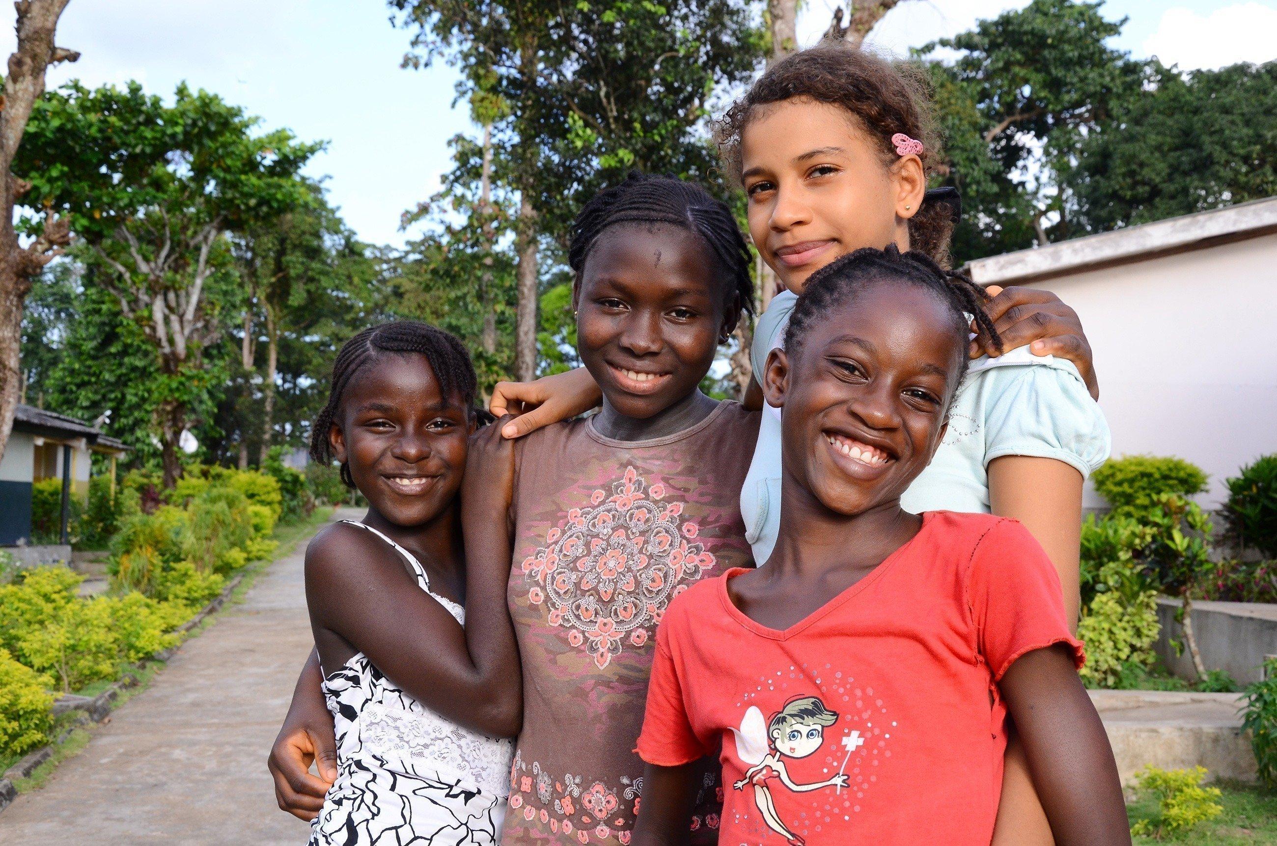 Un groupe de quatre fillettes en train de rire.