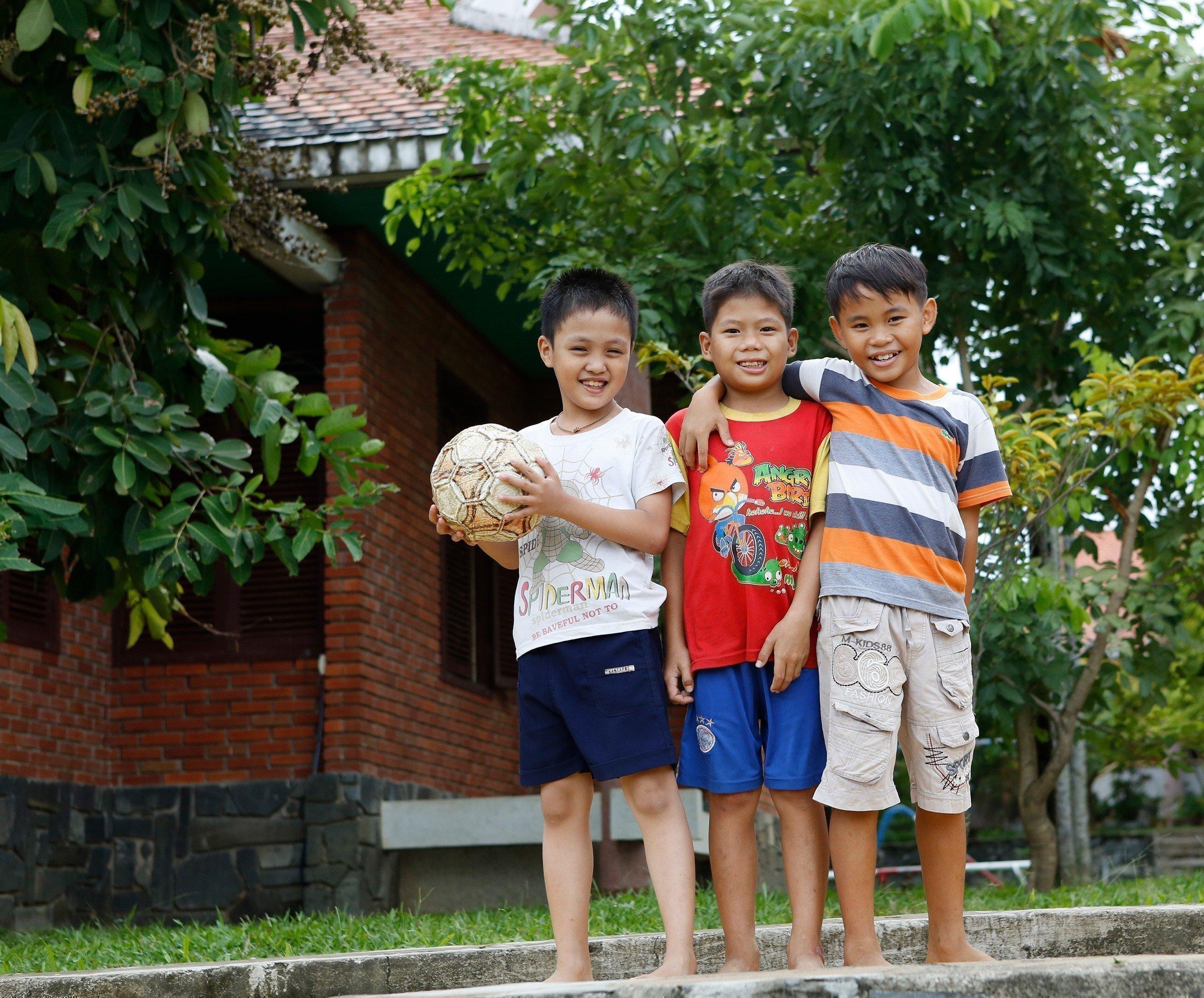 Trois garçons avec un ballon de football.