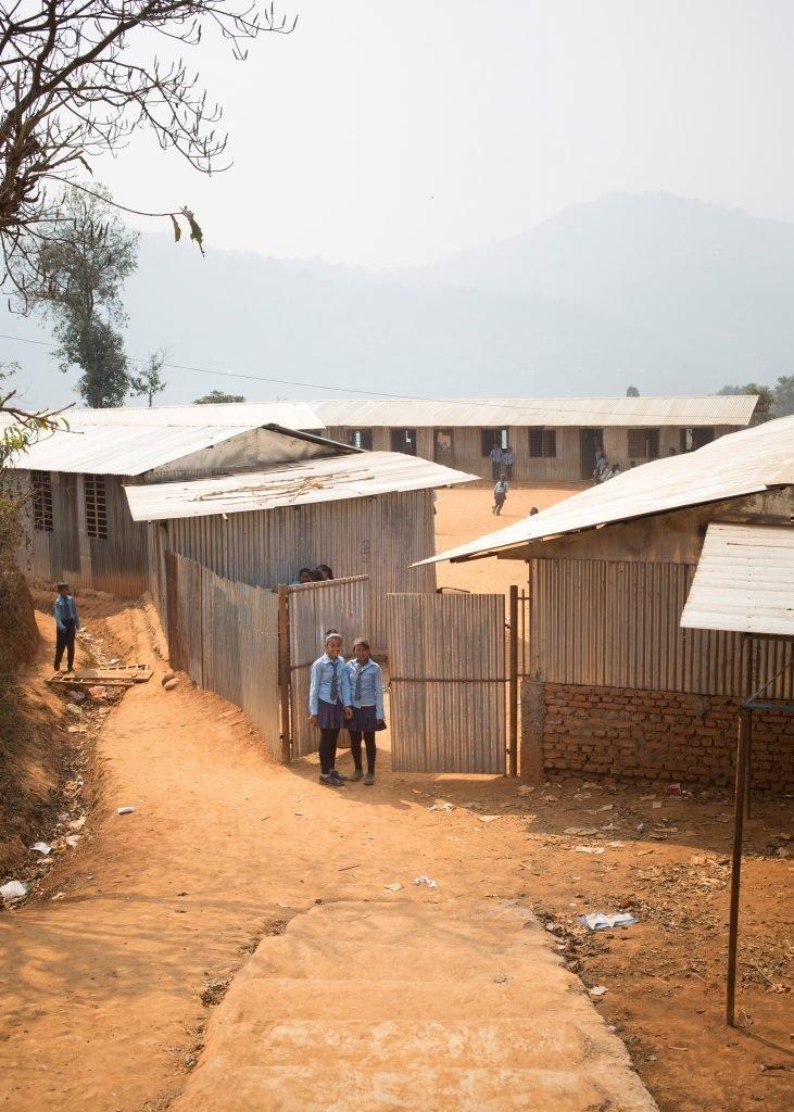 Deux écolières devant un établissement scolaire.