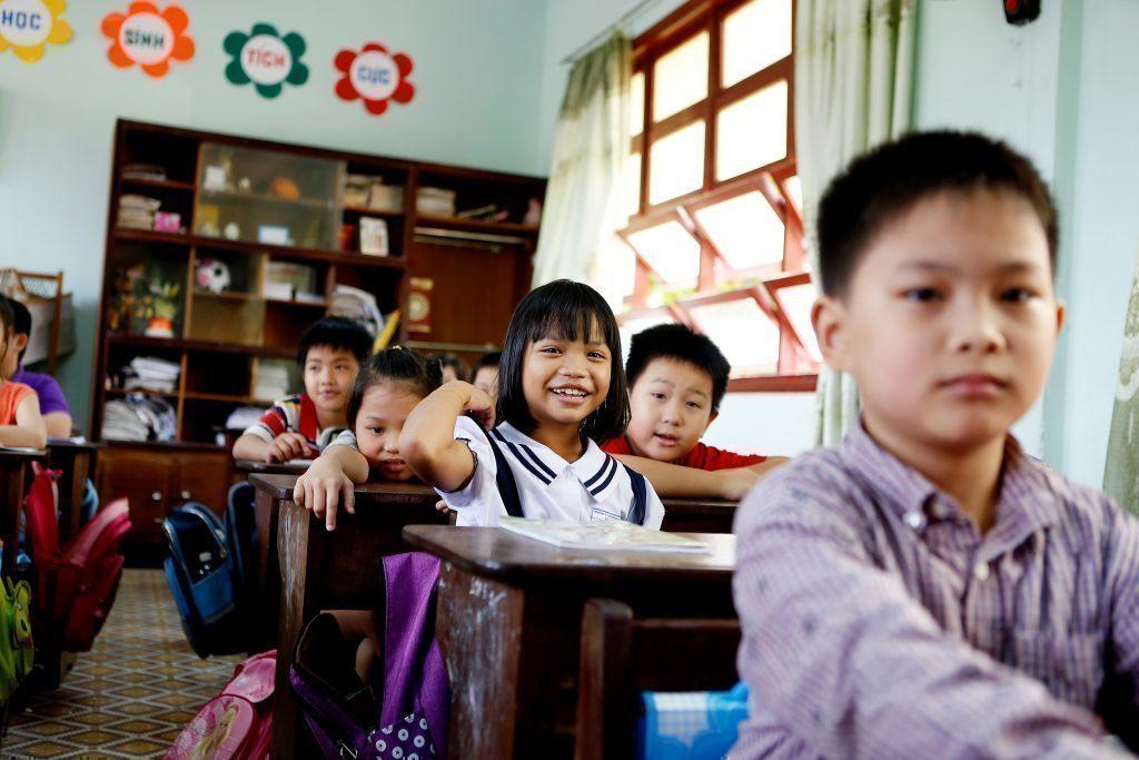 Une petite fille heureuse d'apprendre en classe.