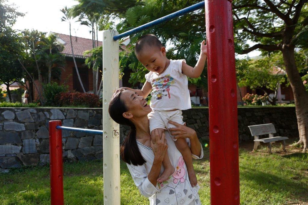 Un jeune enfant s'amusant sur un portique de jeux d'extérieur avec sa mère.