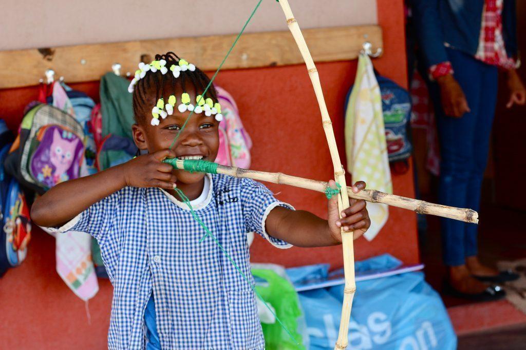 Un enfant en train de jouer avec un arc et une flèche en bois.