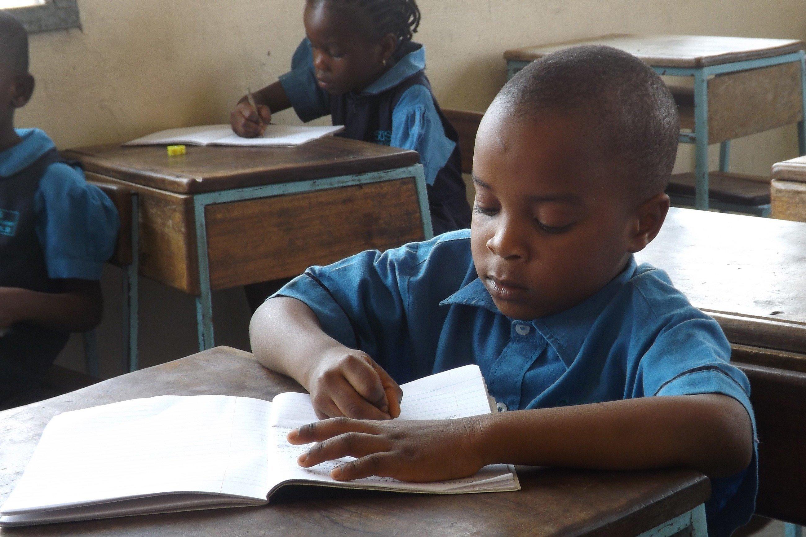 Kleiner Junge schreibt in ein Heft.