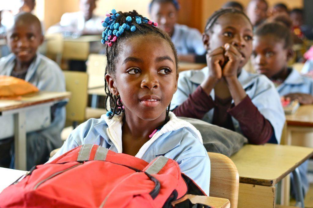 Des écolières avec des barrettes colorées dans les cheveux. Un cartable d'école rouge.