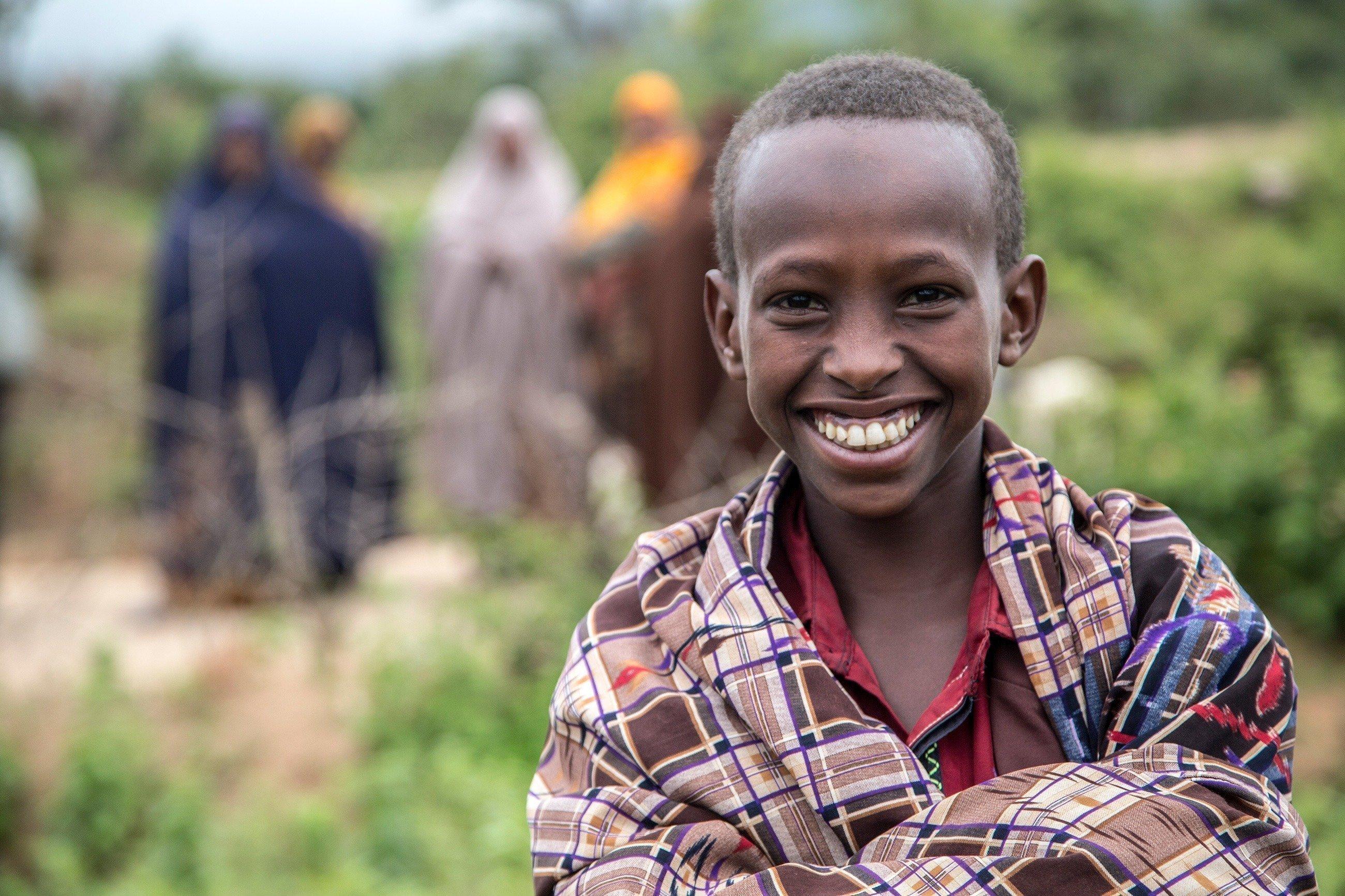 Un garçon africain affichant un large sourire face au photographe.