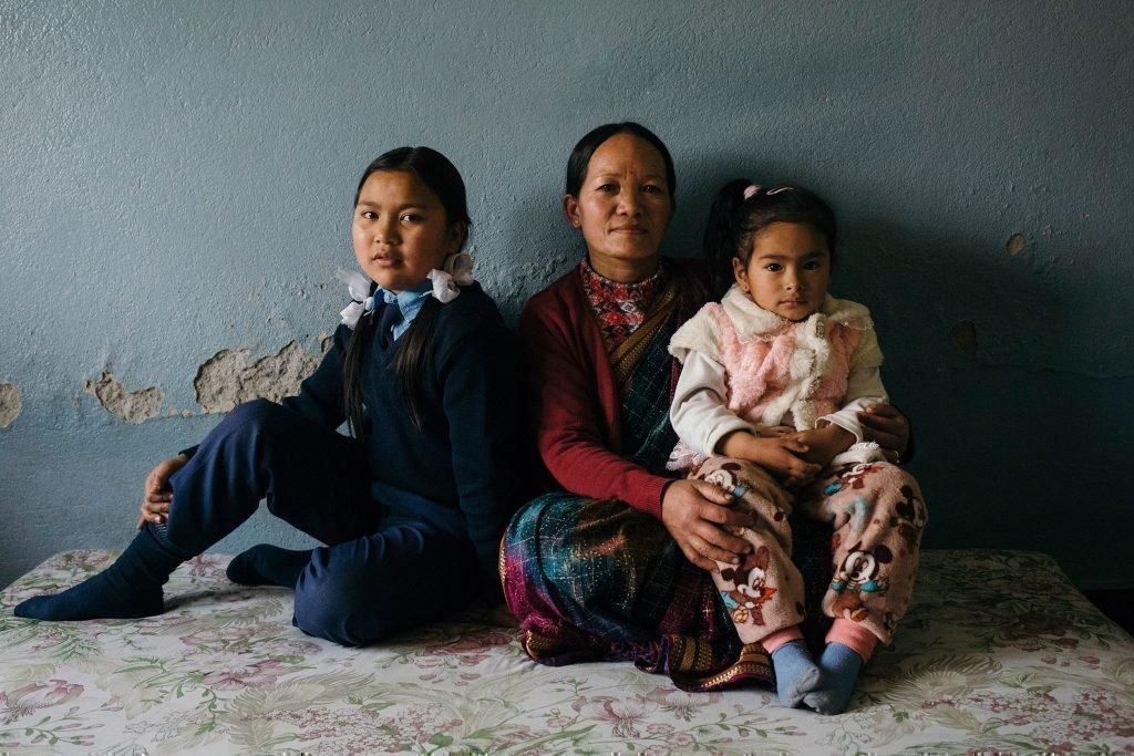 Une famille assise. Une mère avec ses deux enfants.