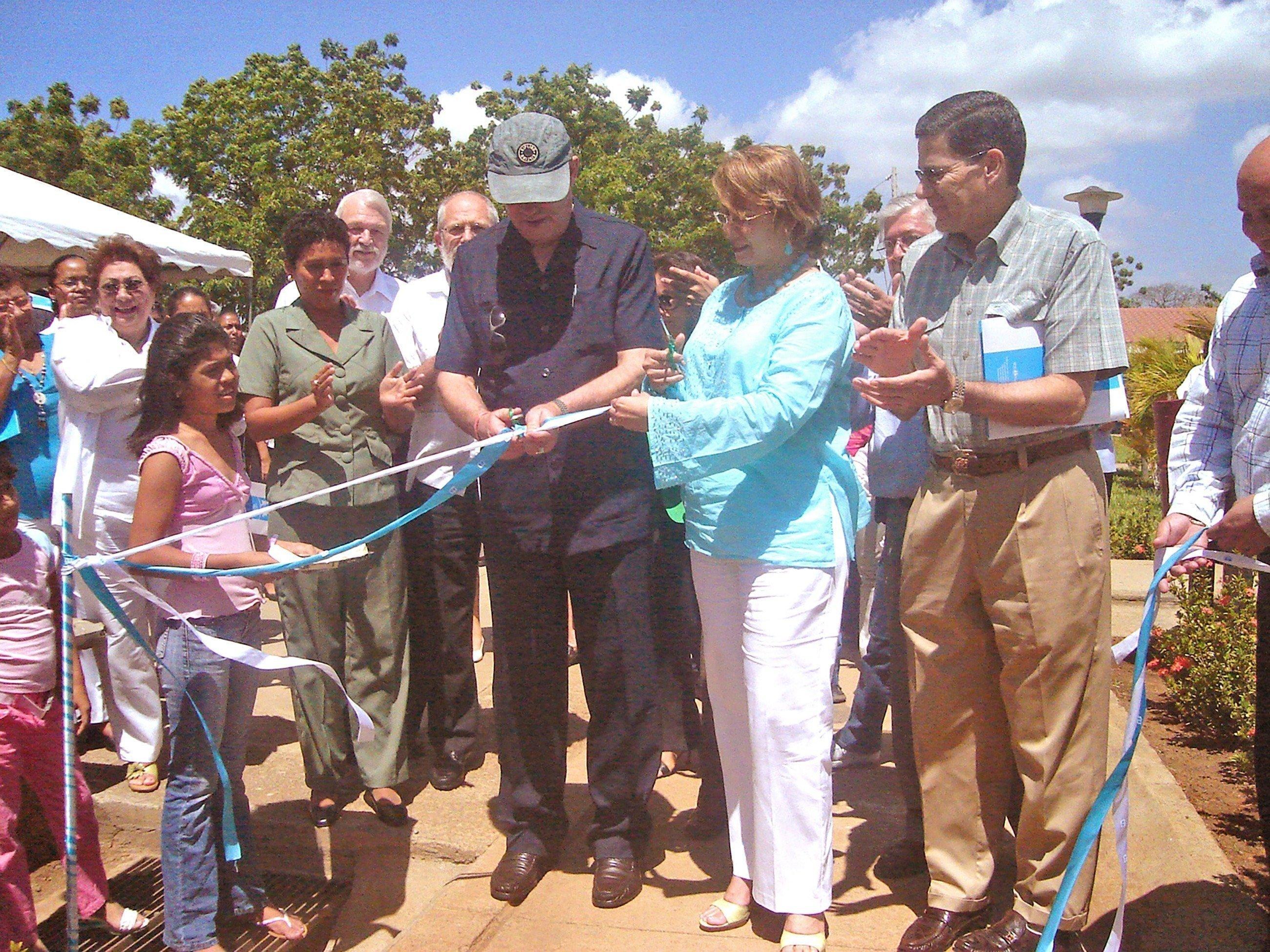 Un collaborateur de SOS Villages d'Enfants en train de couper le ruban à l'aide de ciseaux.