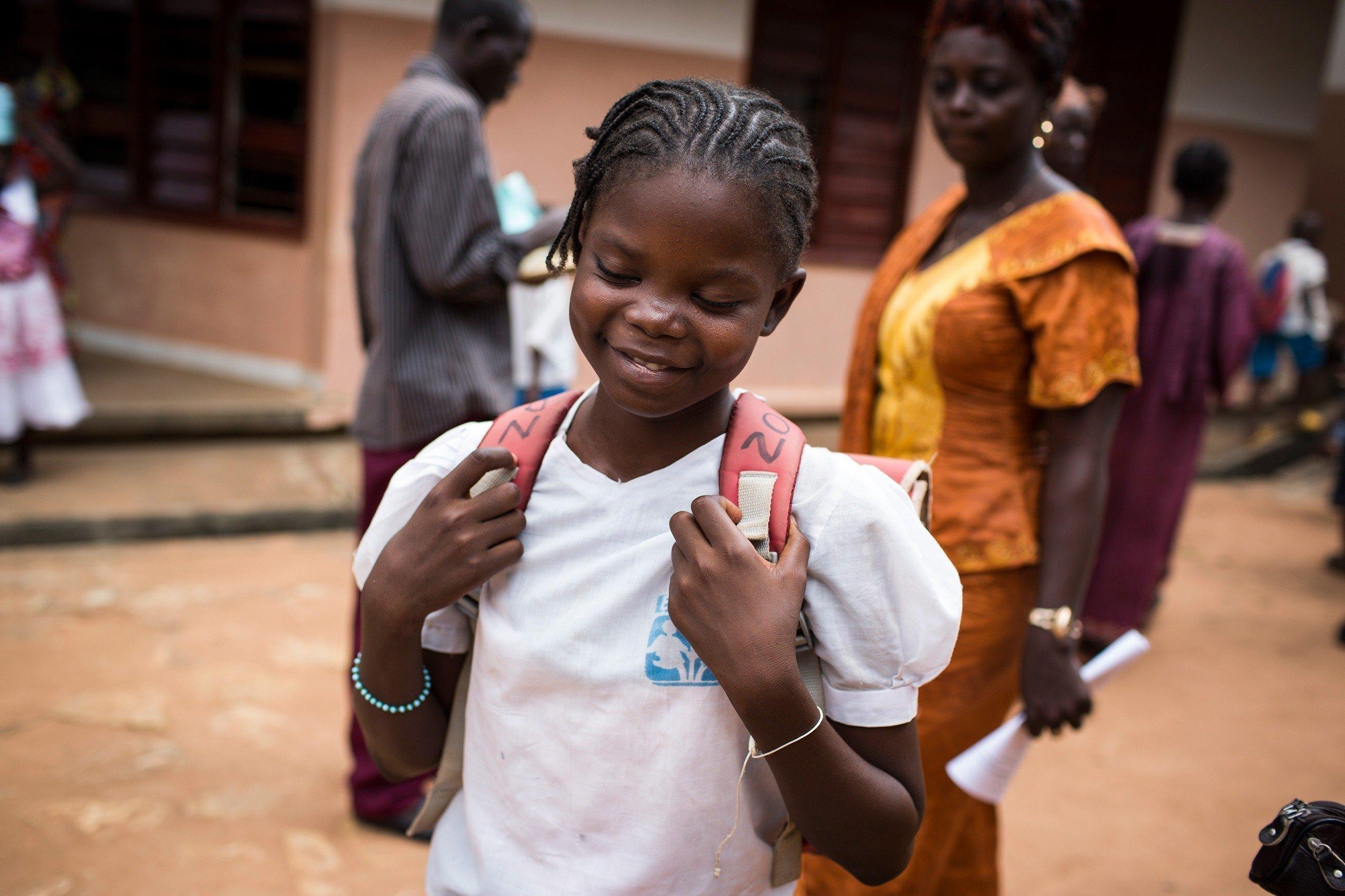 Ein lächelndes Mädchen auf dem Weg zur Schule.