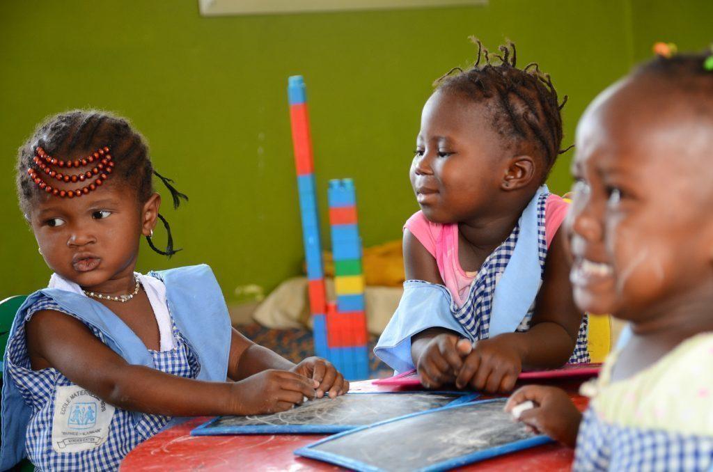 Trois fillettes à une table en train de jouer.