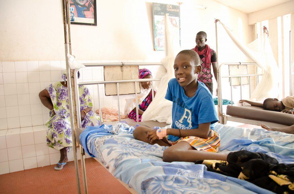Un garçon riant sur un lit d'hôpital.