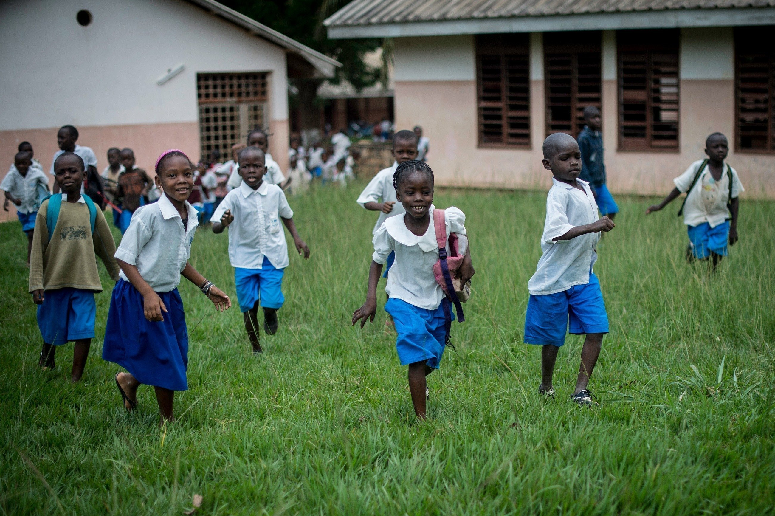 Kinder rennen nach Schulschluss aus der Schule raus.