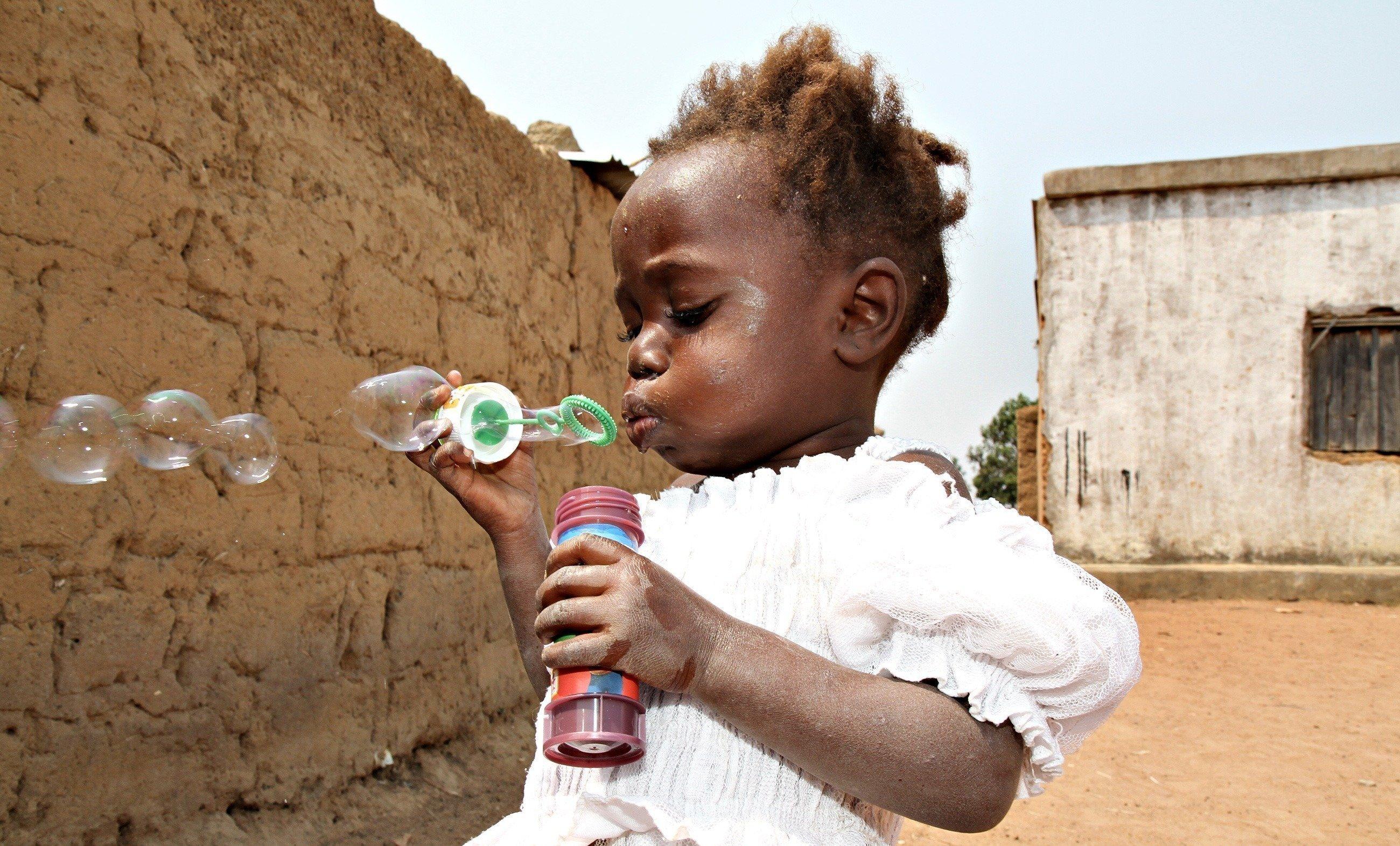 Ein kleines Mädchen mit einem weißen Kleid spielt mit Seifenblasen.