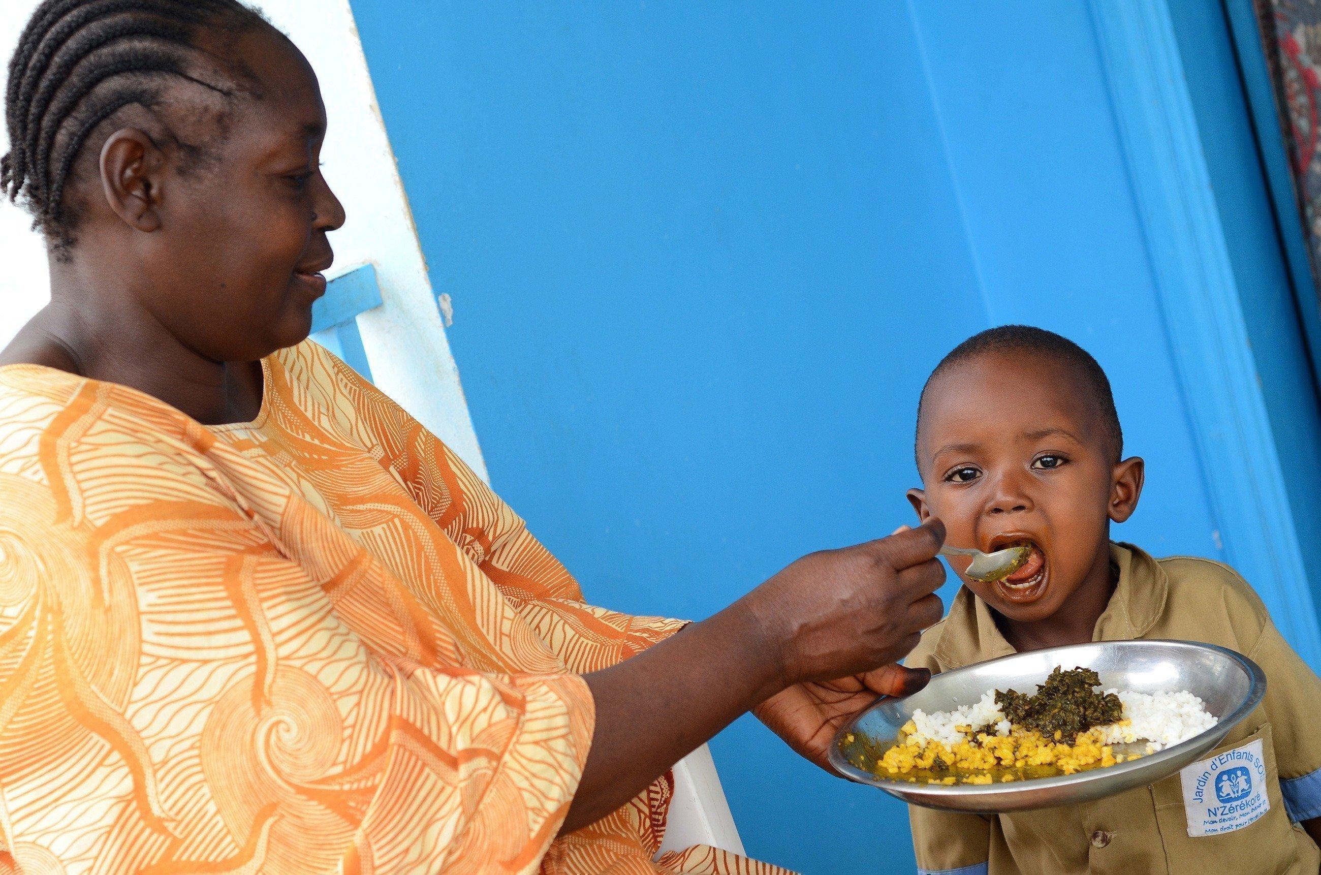Eine SOS-Kinderdorf Mutter füttert ein Kind.