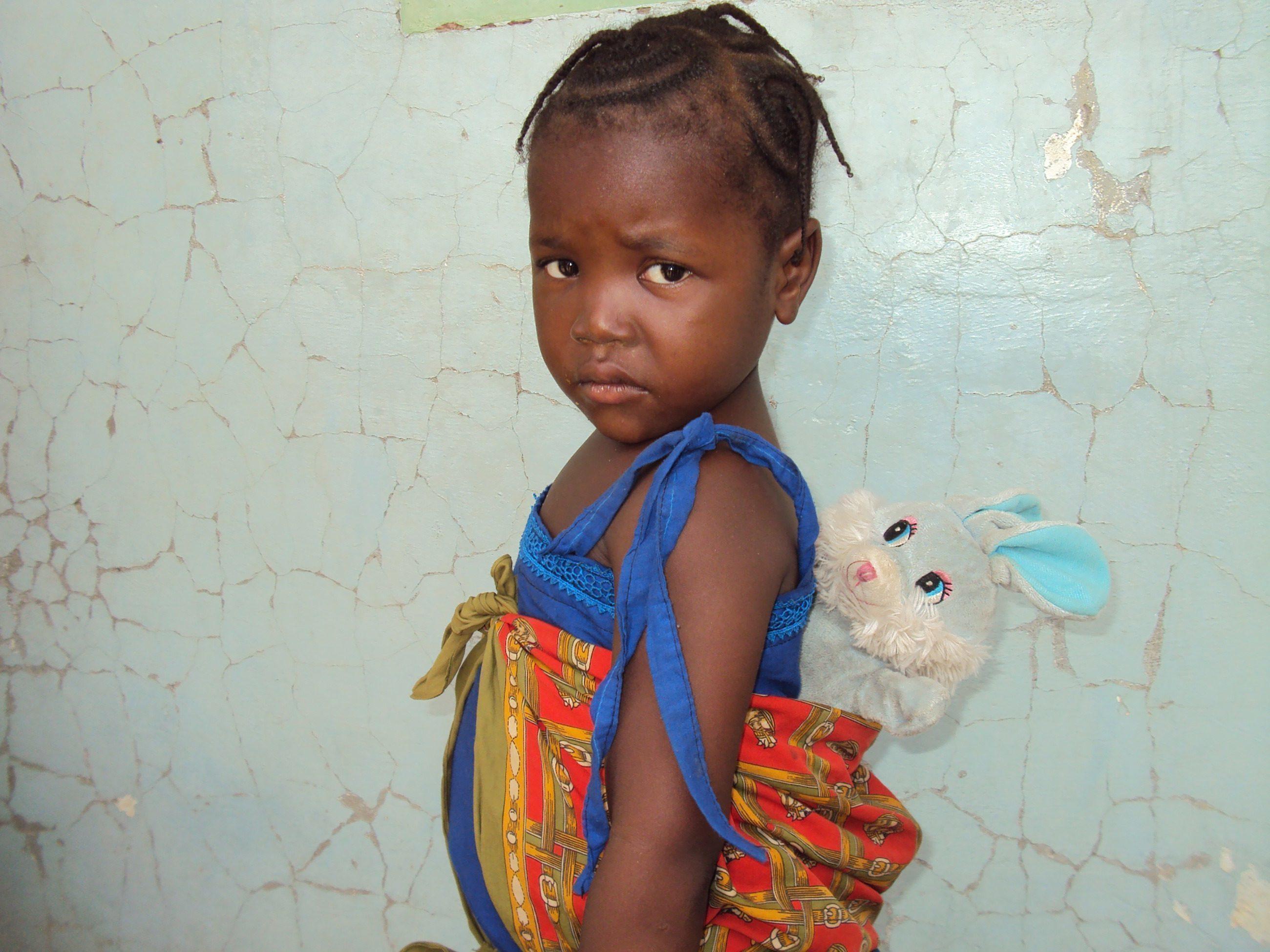 Une petite fille africaine au regard triste avec une peluche dans son sac à dos.