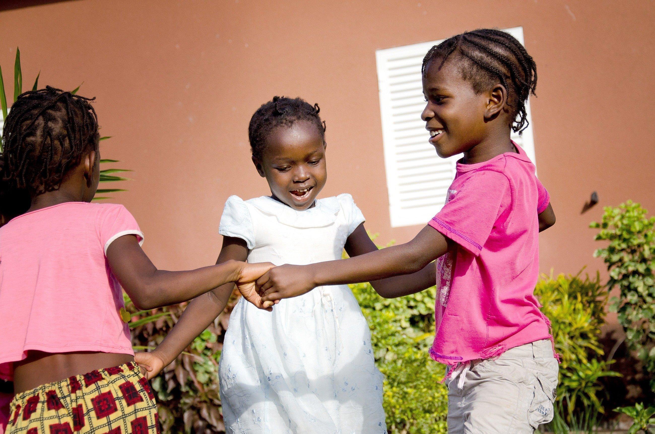Trois petites filles dansent en cercle.