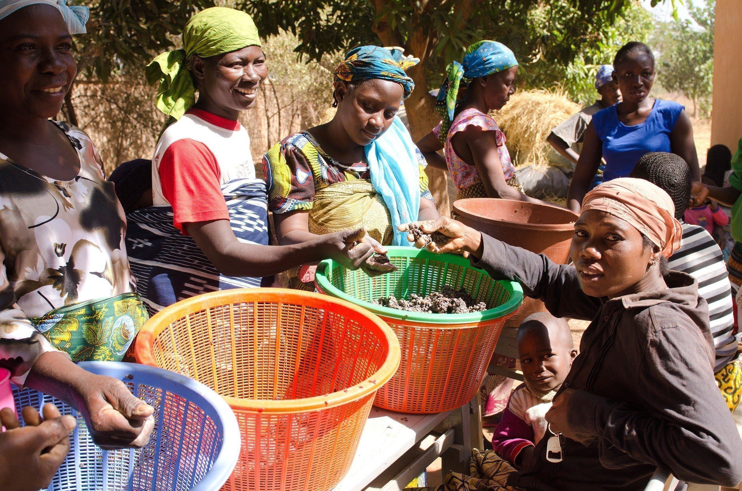Un groupe de femmes avec des corbeilles pleines de légumes.