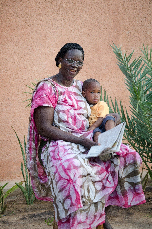Une maman SOS lit un livre à un enfant.