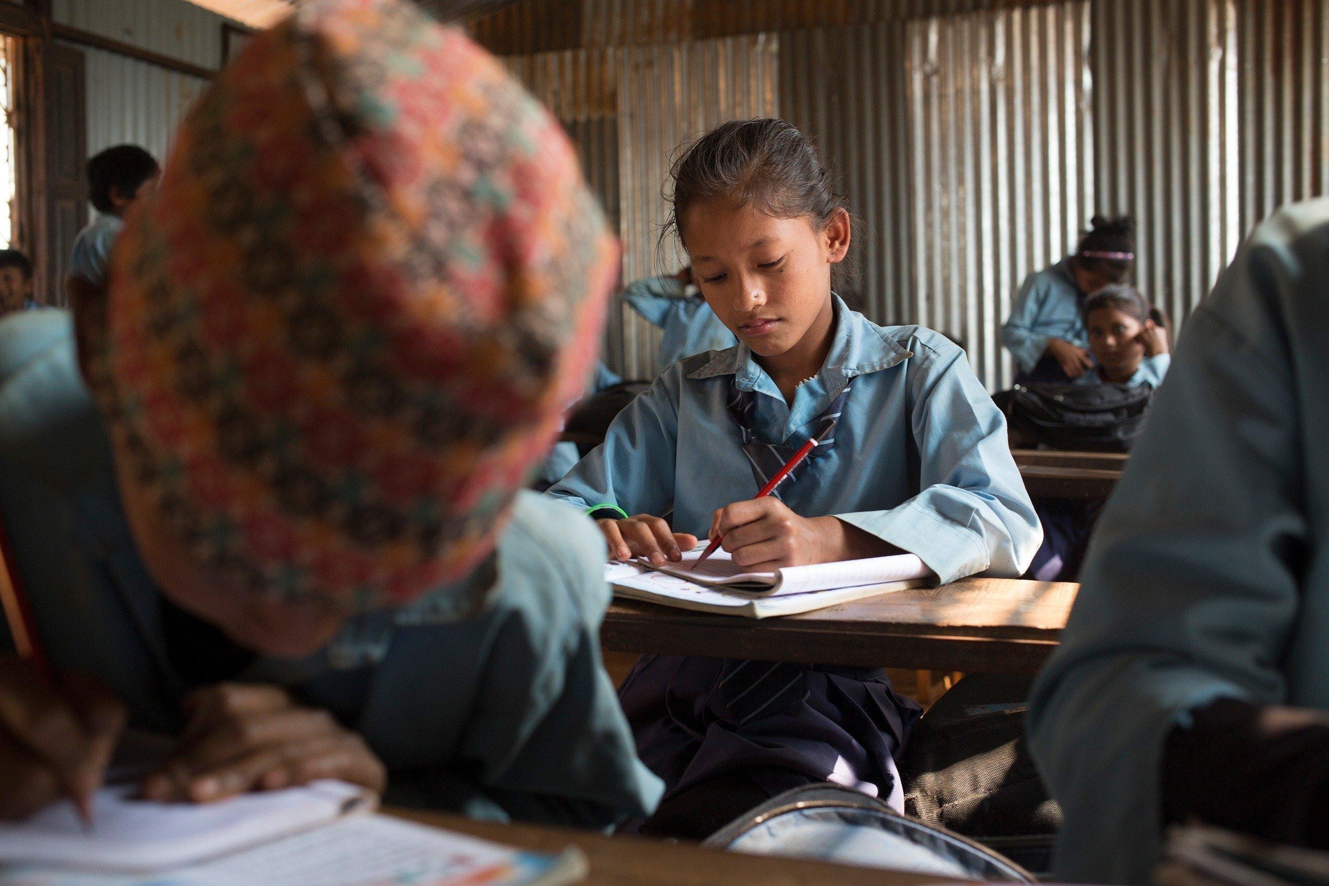Une petite fille népalaise, assise à l'école, écrit dans son cahier.