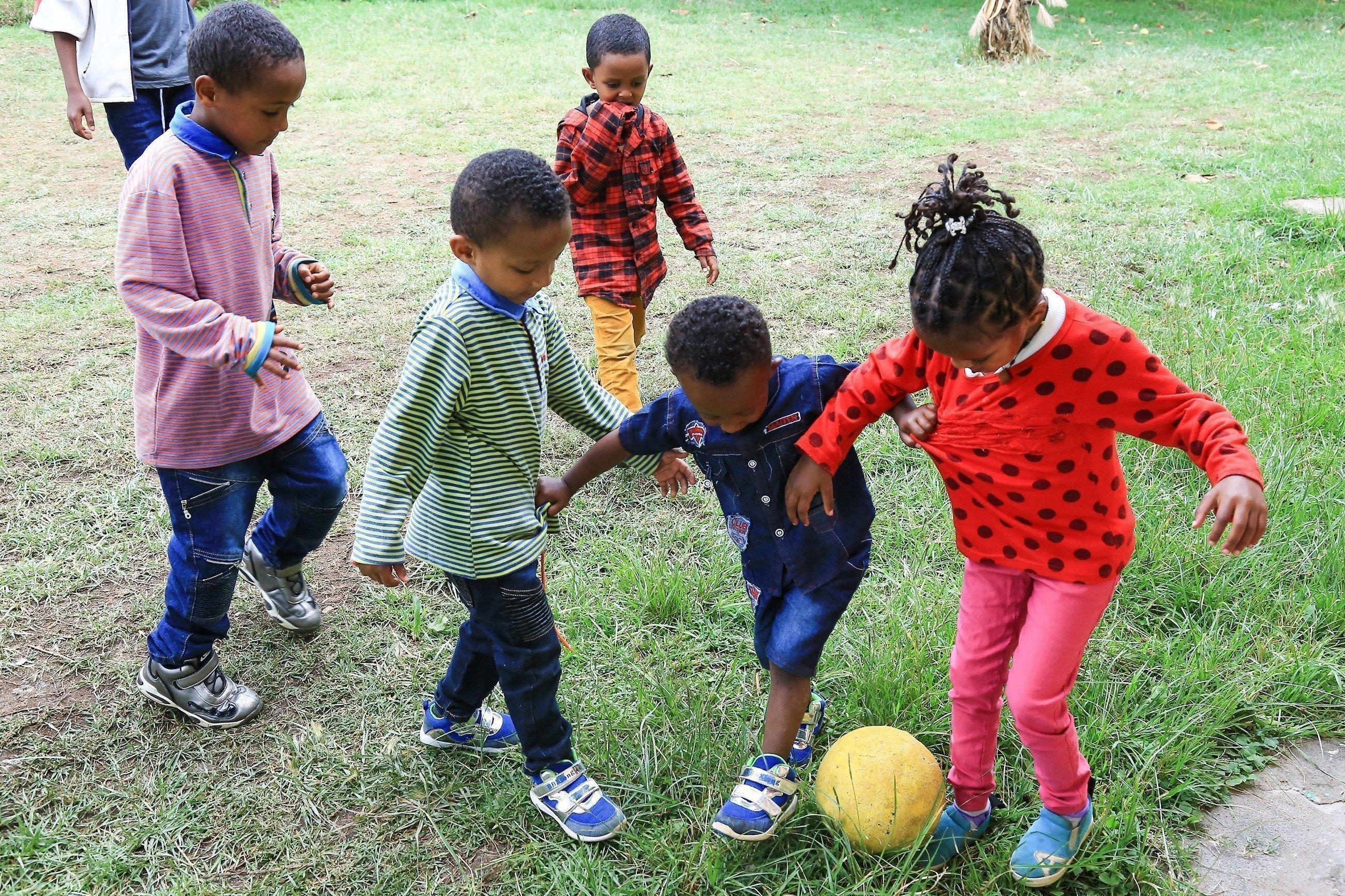 Des enfants africains jouent au football.
