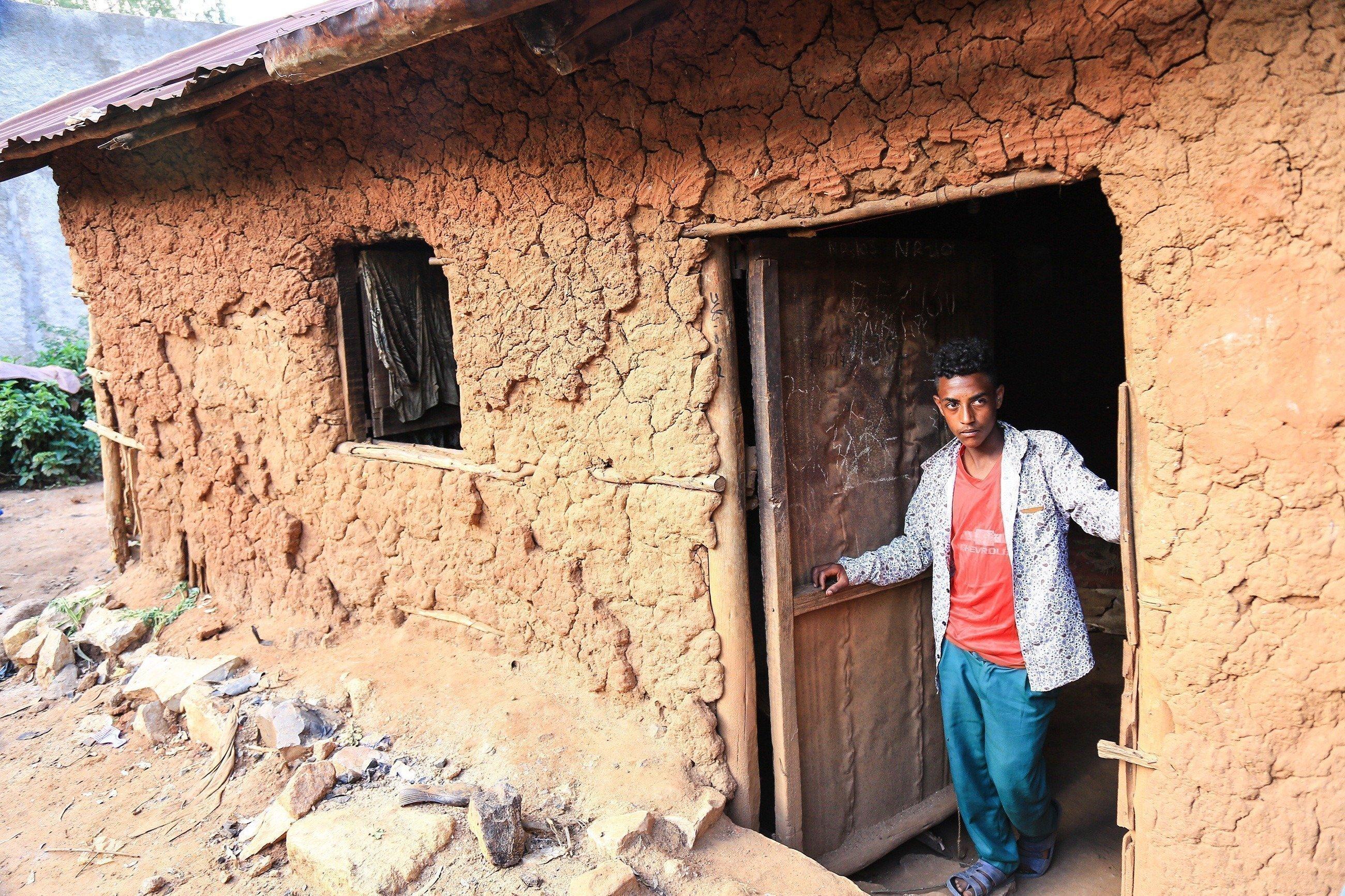 Un jeune garçon dans l'entrée d'une maison en terre.