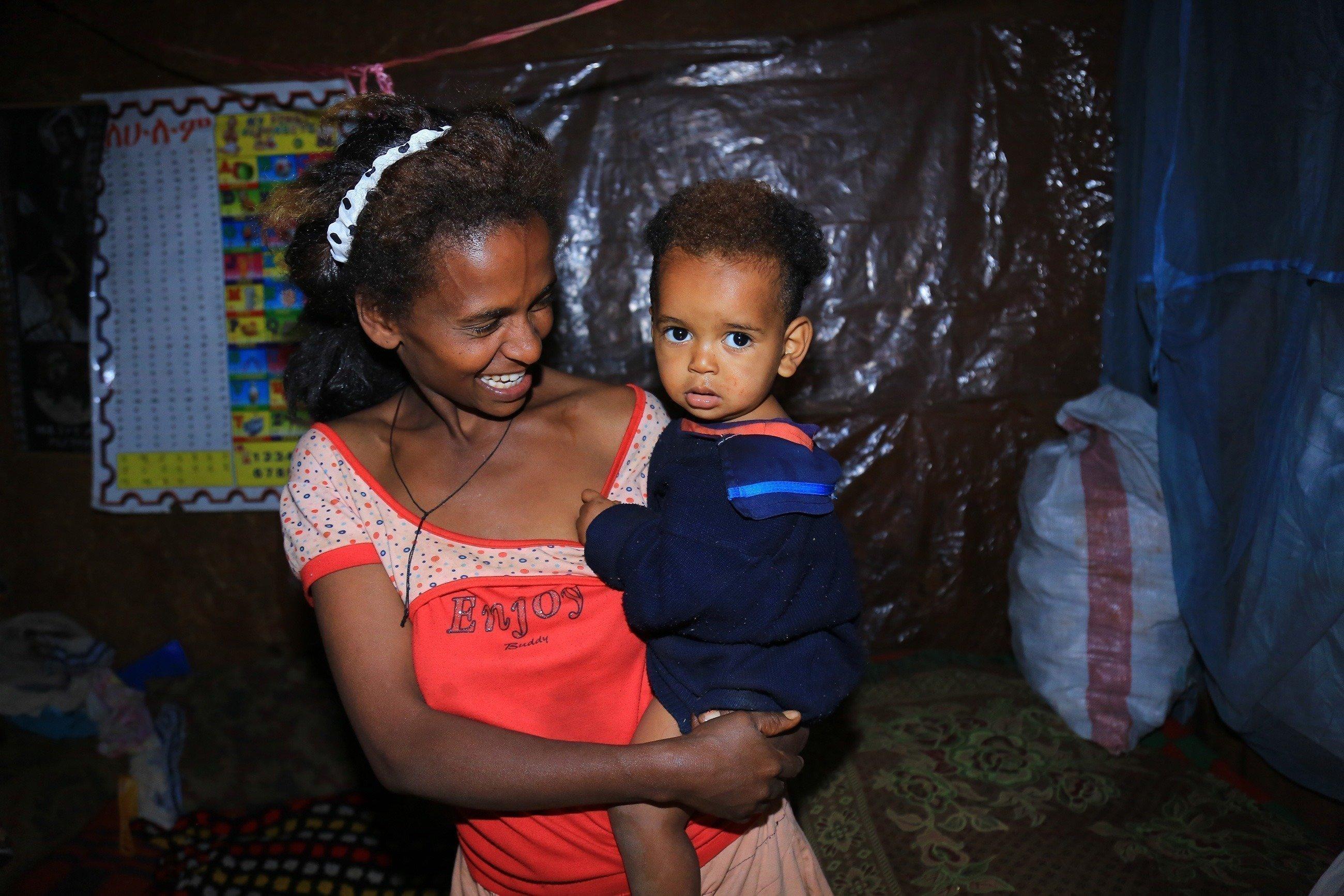 Le sourire d'une mère tenant un enfant africain dans ses bras.