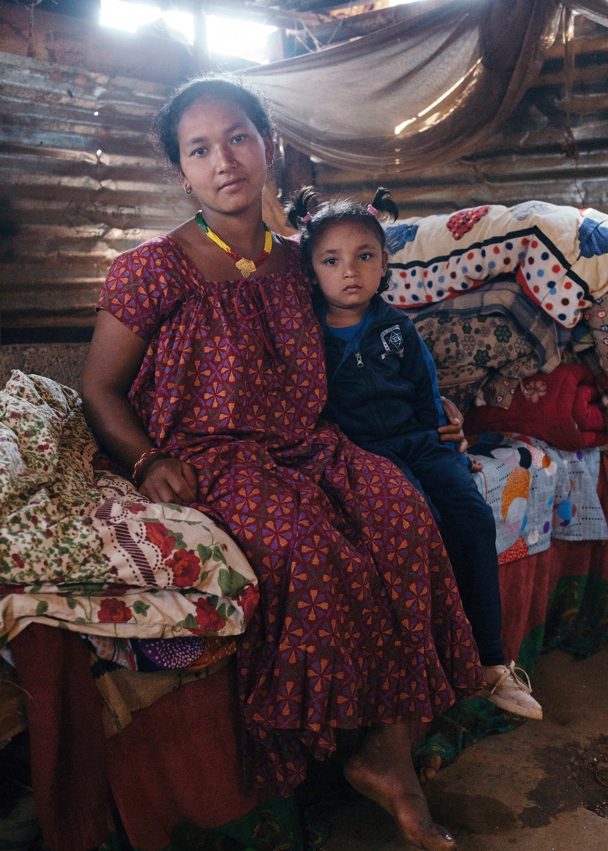 Une mère népalaise tient sa fille dans ses bras.