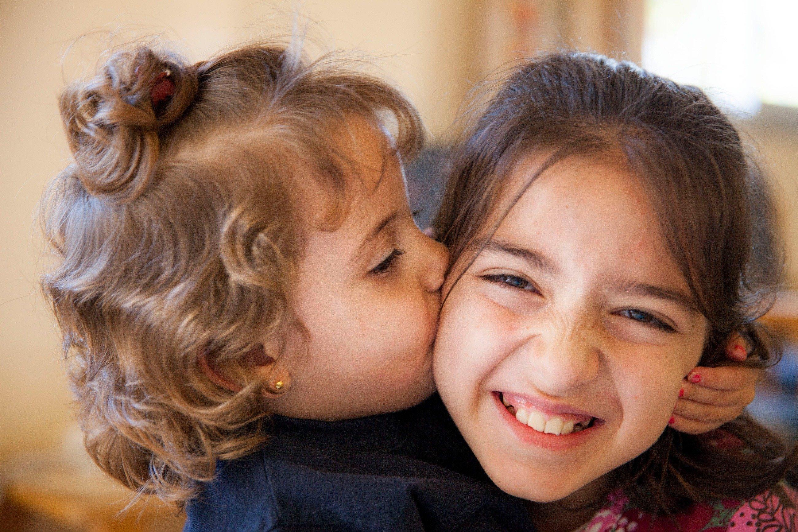 Une petite fille embrasse une autre fillette sur la joue.