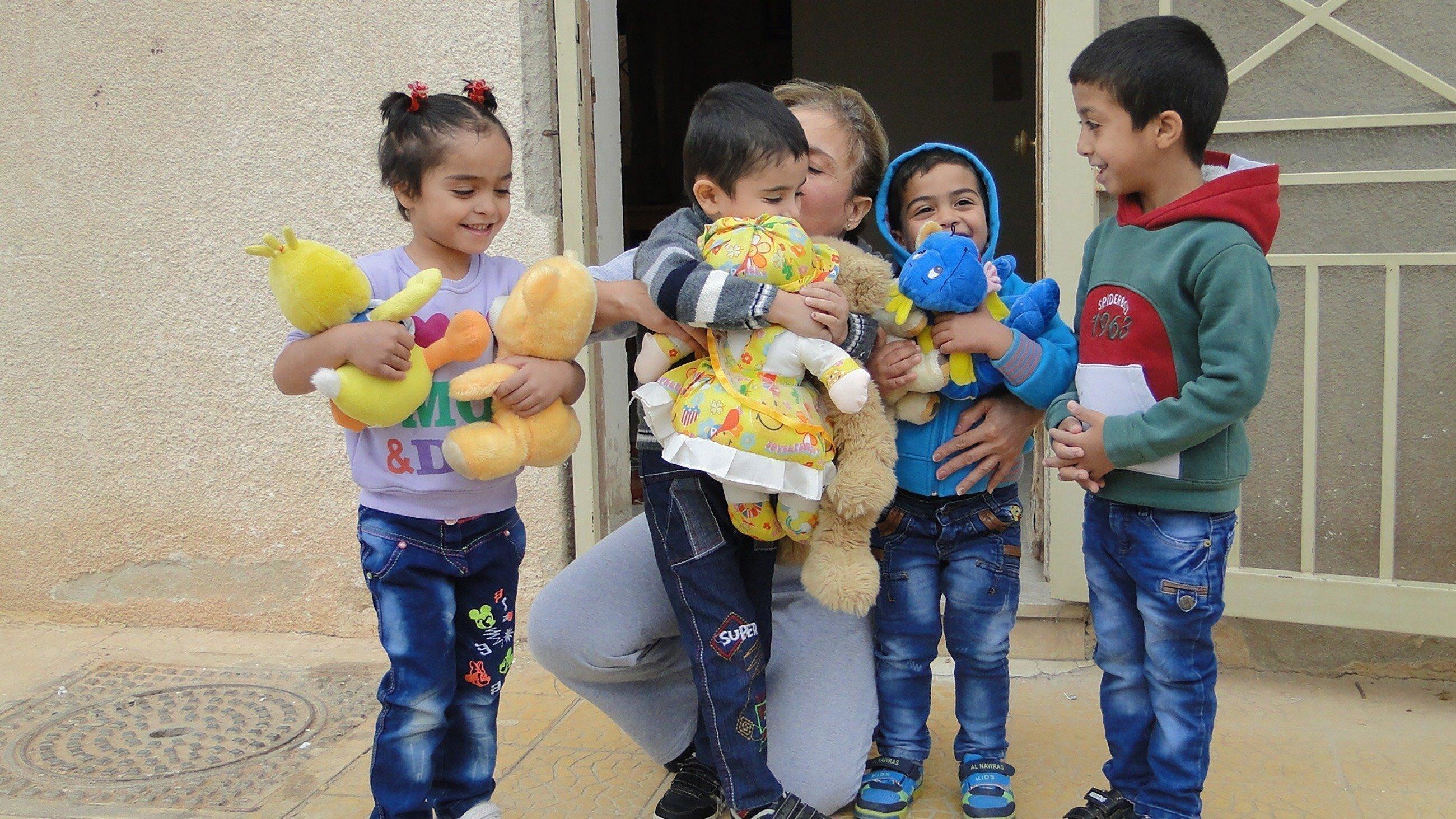 Des enfants heureux devant des peluches.