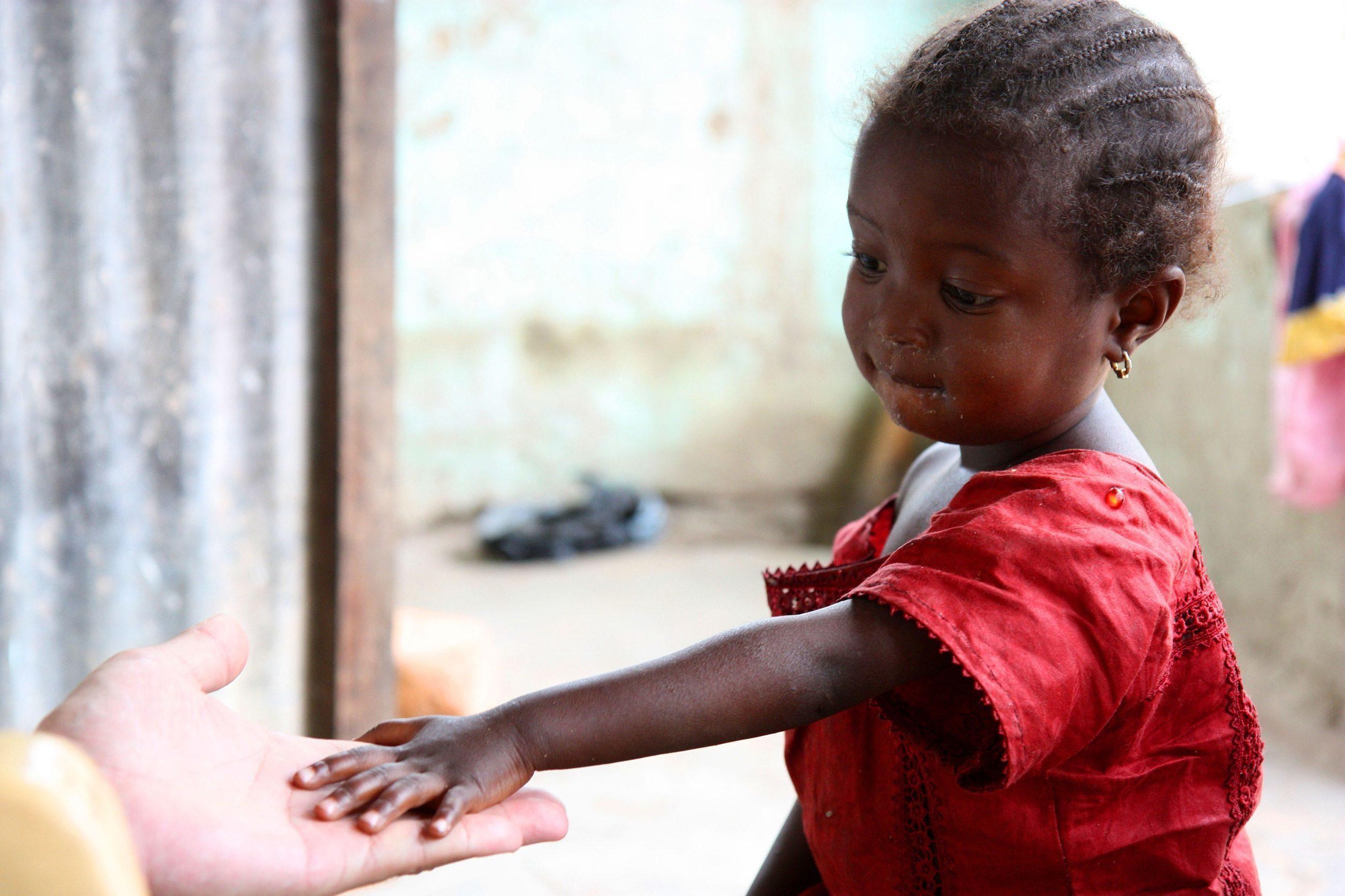 Une fillette africaine tend la main à un parrain.