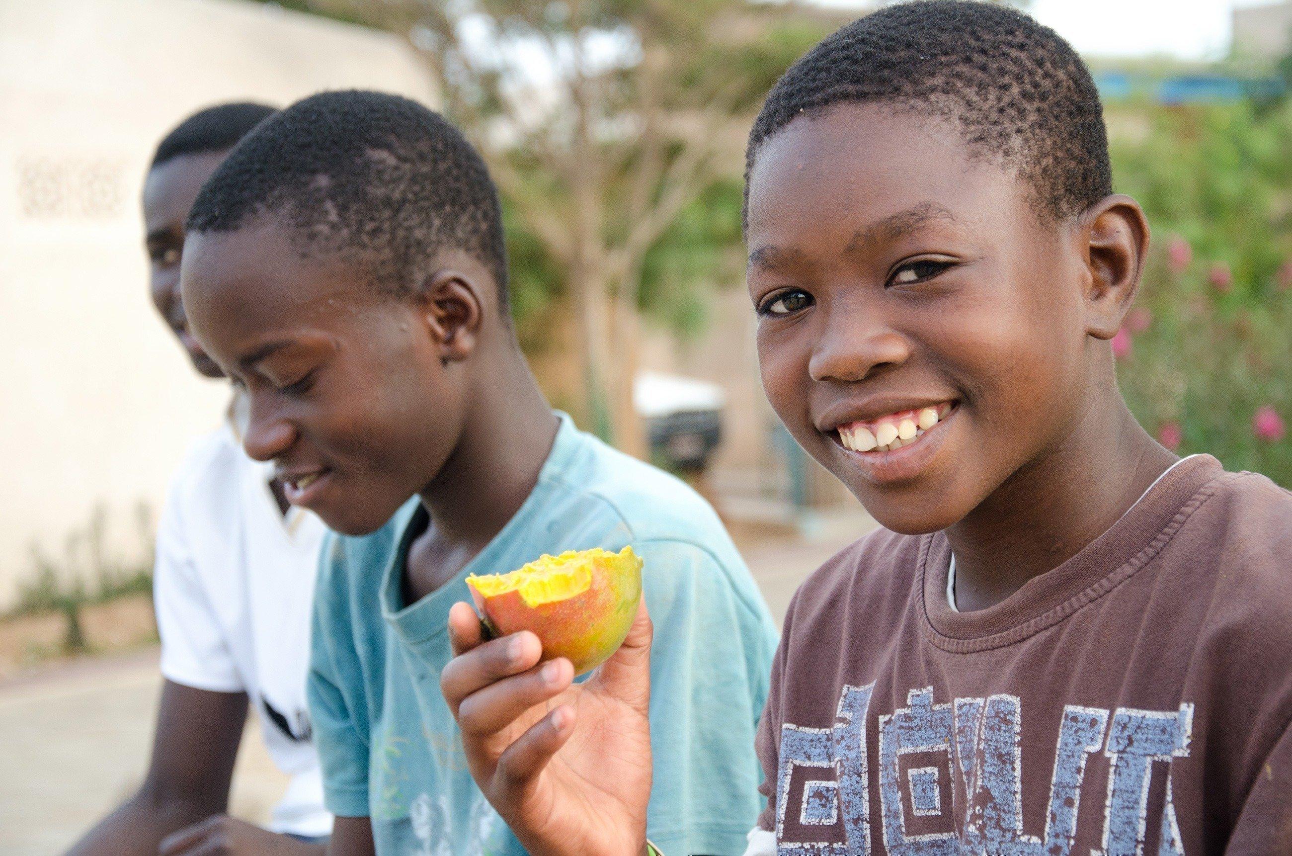 Un enfant mange un fruit.