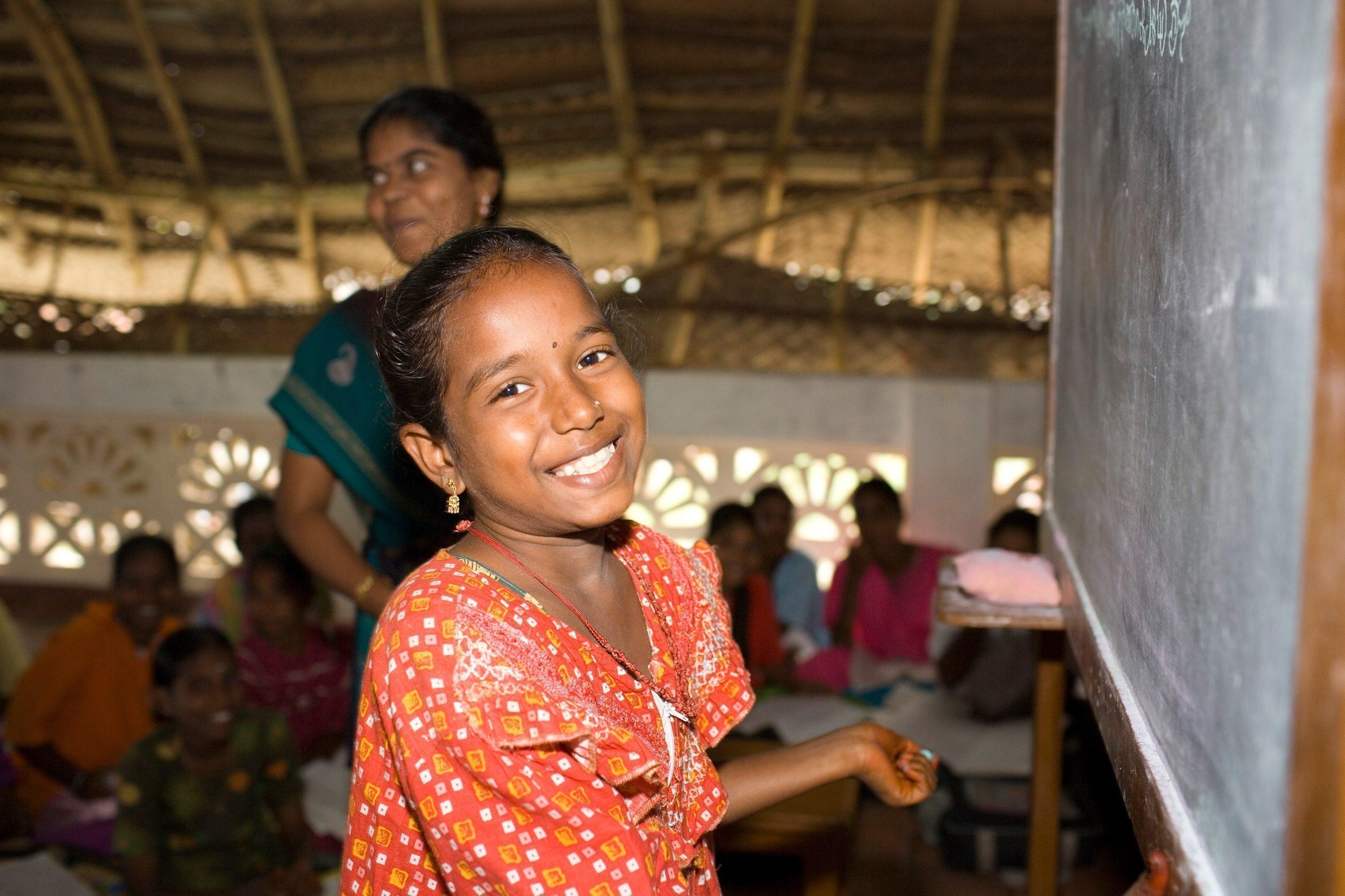 Une petite fille indienne souriante, au tableau.