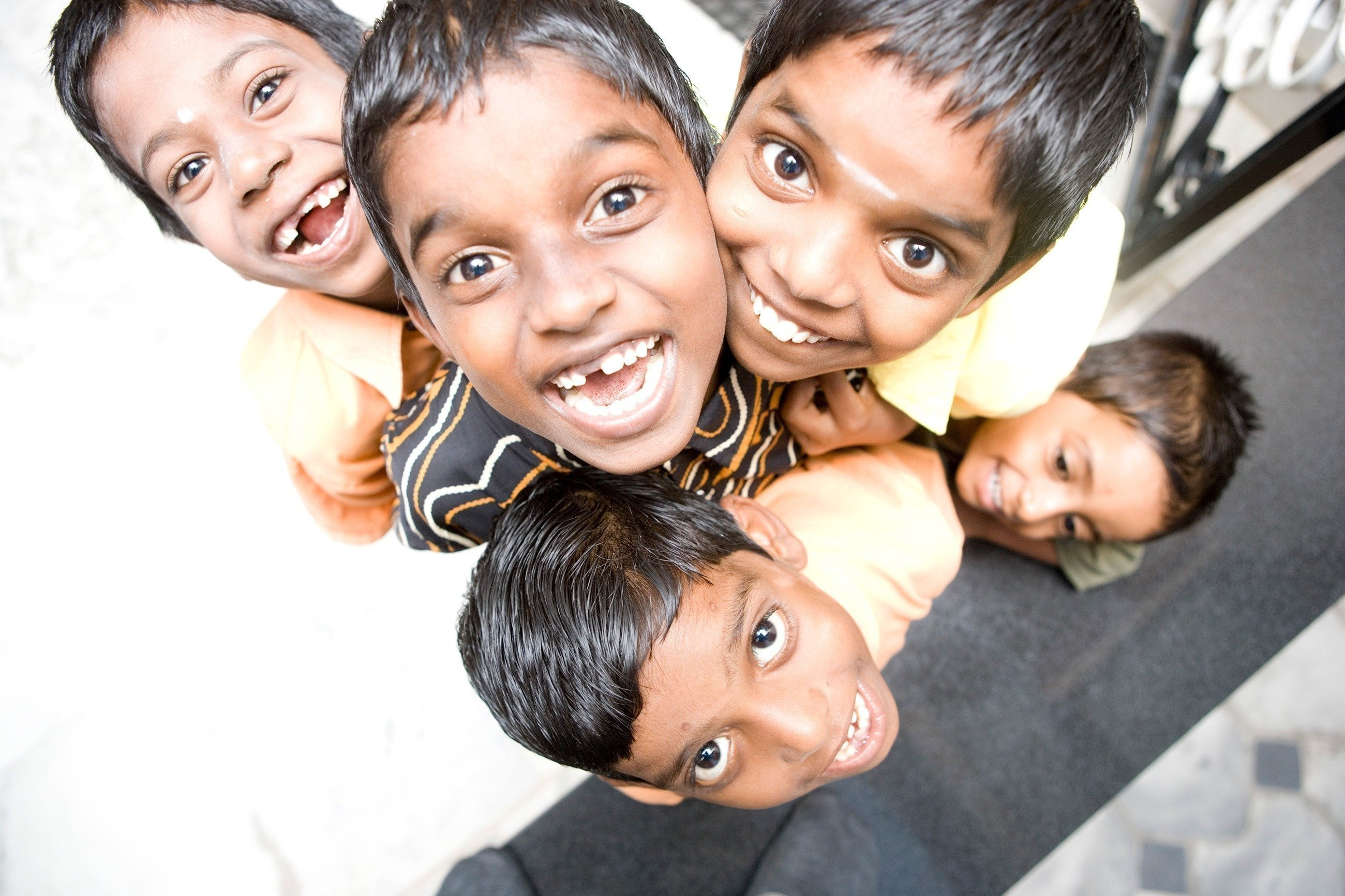 Des enfants indiens regardent en haut, vers l'appareil photo, en riant.