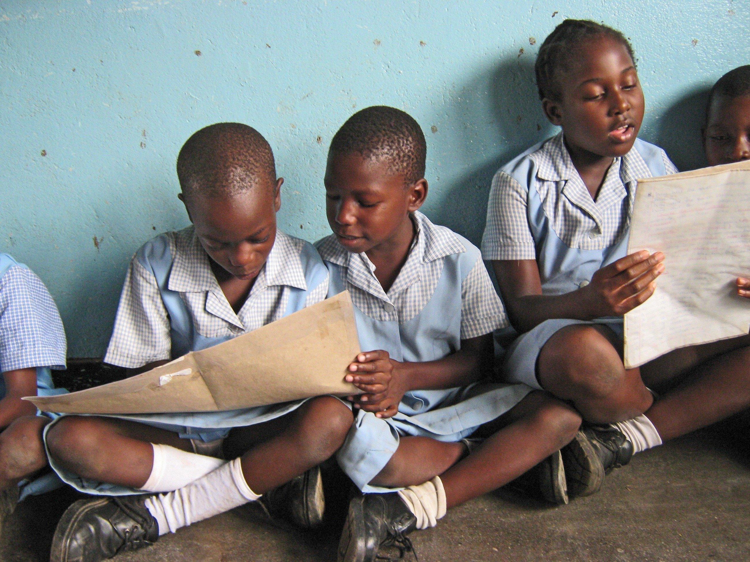 Des petites filles en robes bleues lisent un cahier.