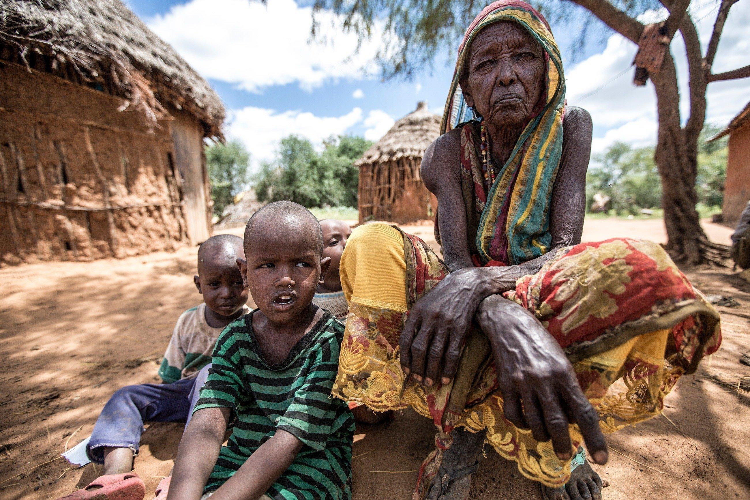 Une femme âgée assise à l'ombre d'un arbre avec deux jeunes enfants.