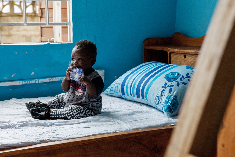 Un petit garçon africain est assis sur le lit et mordille un bout de plastique.