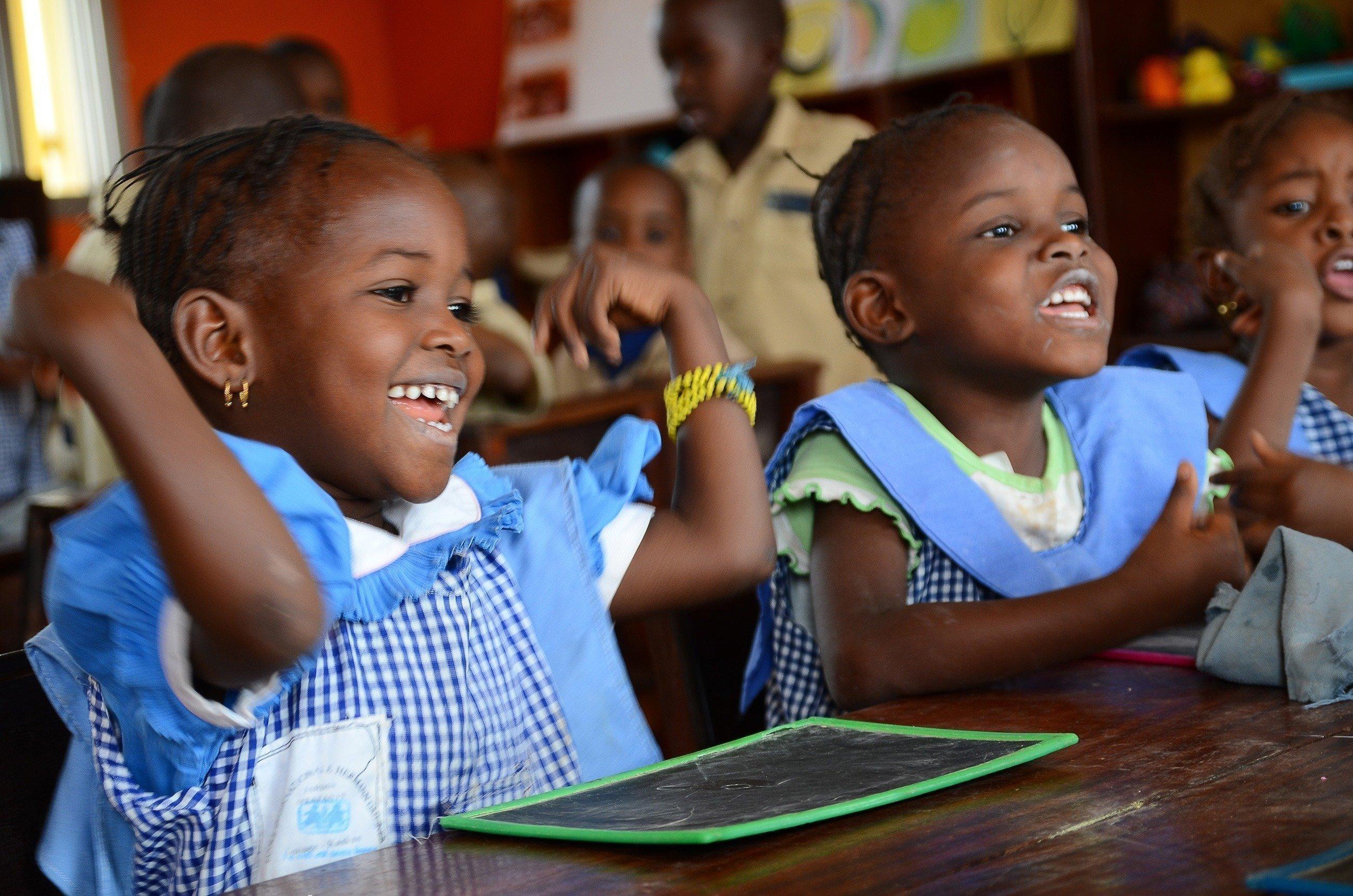 Deux petites filles à l'école qui prennent plaisir à apprendre.