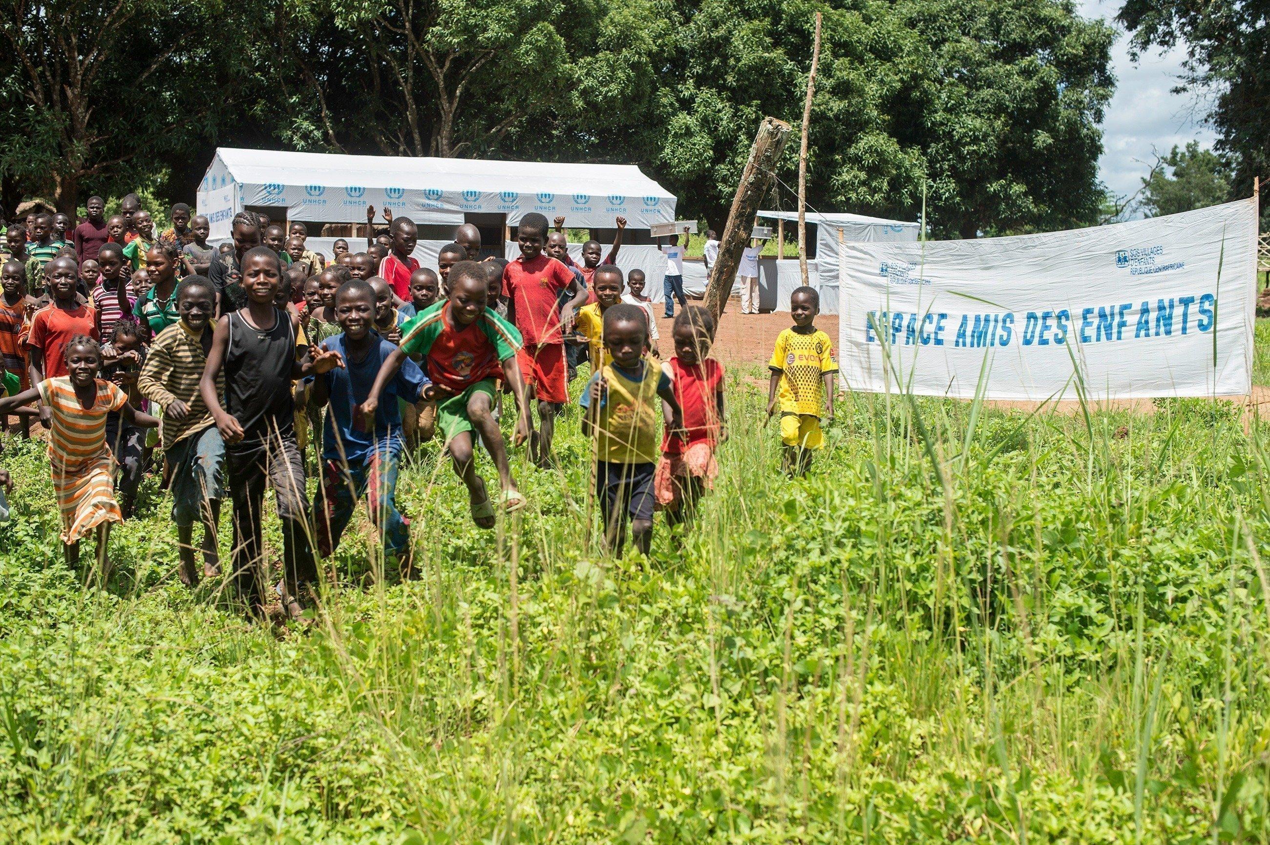 Une foule d'enfants court en direction de l'appareil photo. Un panneau d'entrée montre un slogan de SOS Villages d'Enfants.