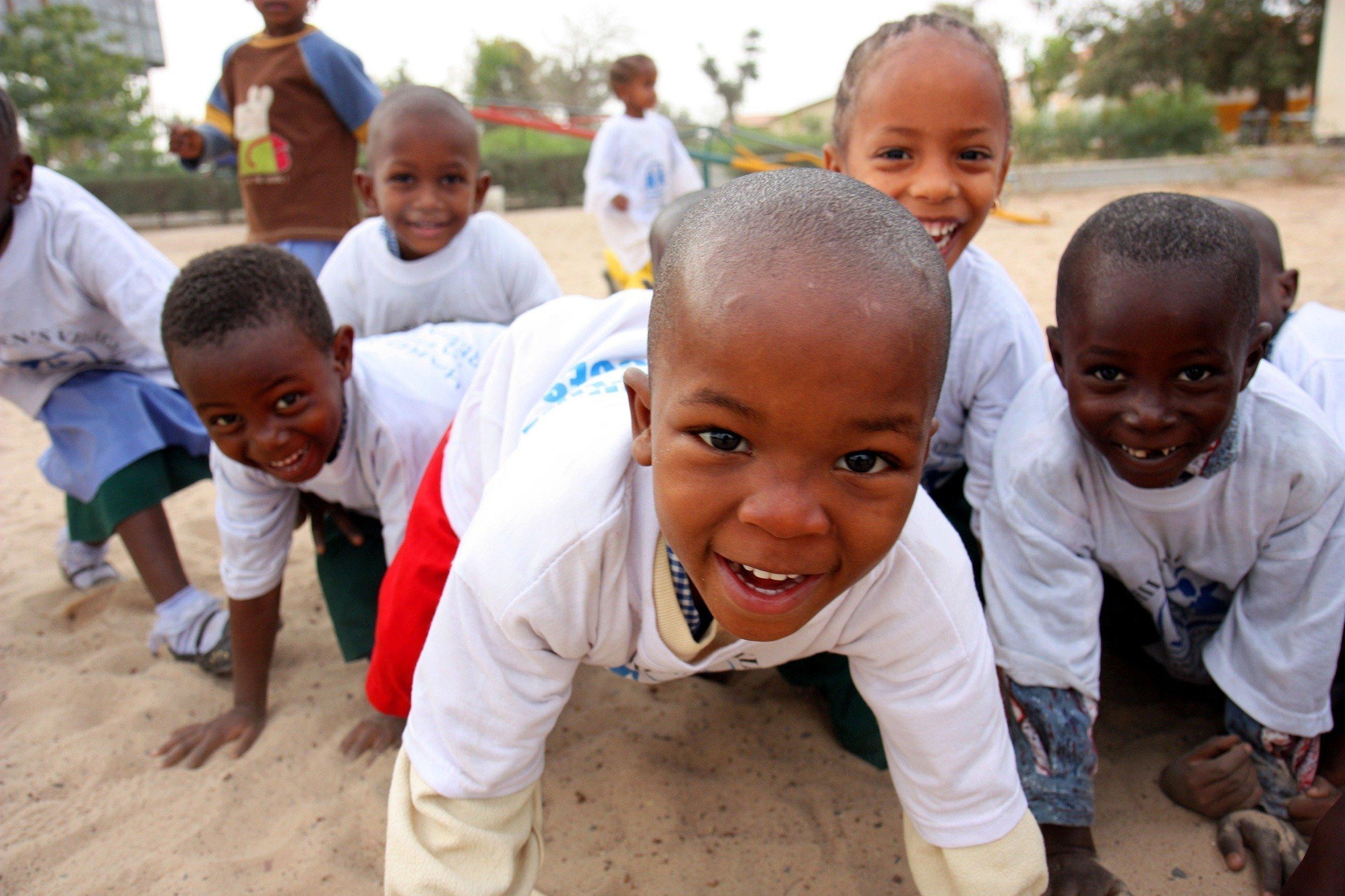 Plusieurs enfants jouent en riant devant l'appareil photo.