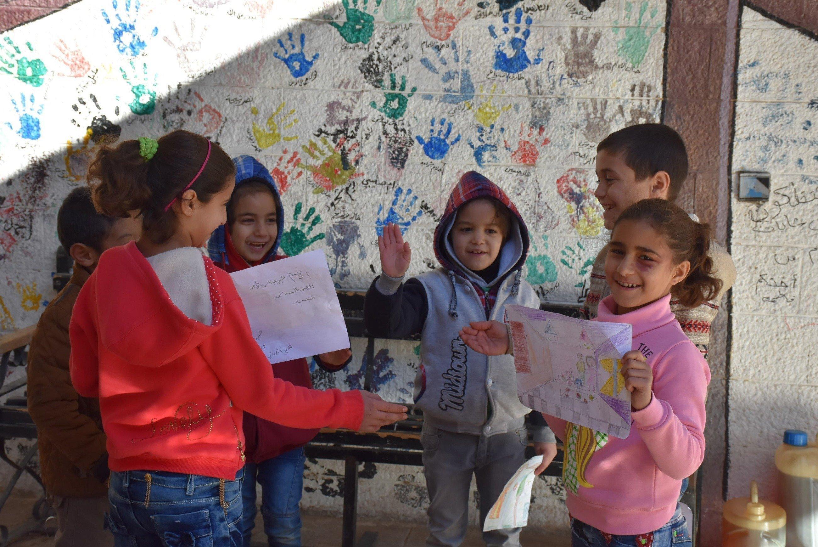 Des enfants jouent avec de la peinture sur leurs mains.