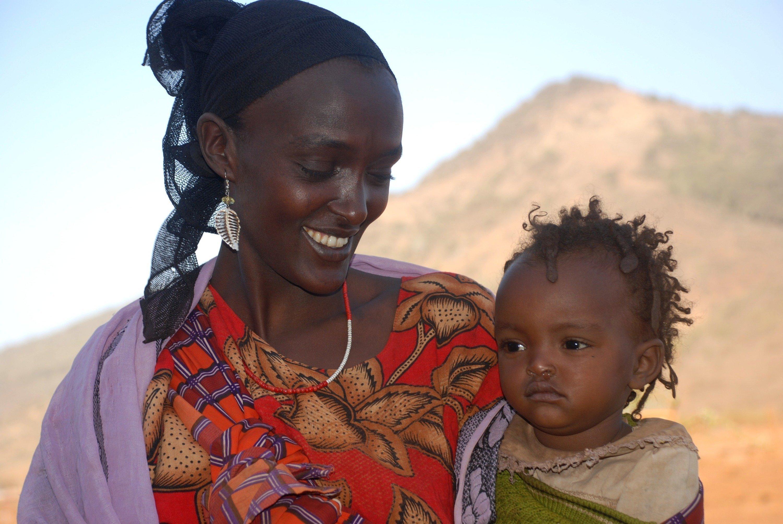 Eine SOS Kinderdorf Mutter mit einem Kleinkind auf dem Arm.
