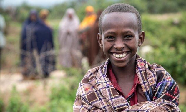 Afrikanischer Junge lächelt breit in die Kamera.