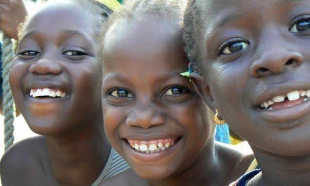 Drei Mädchen lächeln.
