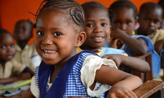 Ein Mädchen in blauer Schuluniform lacht.
