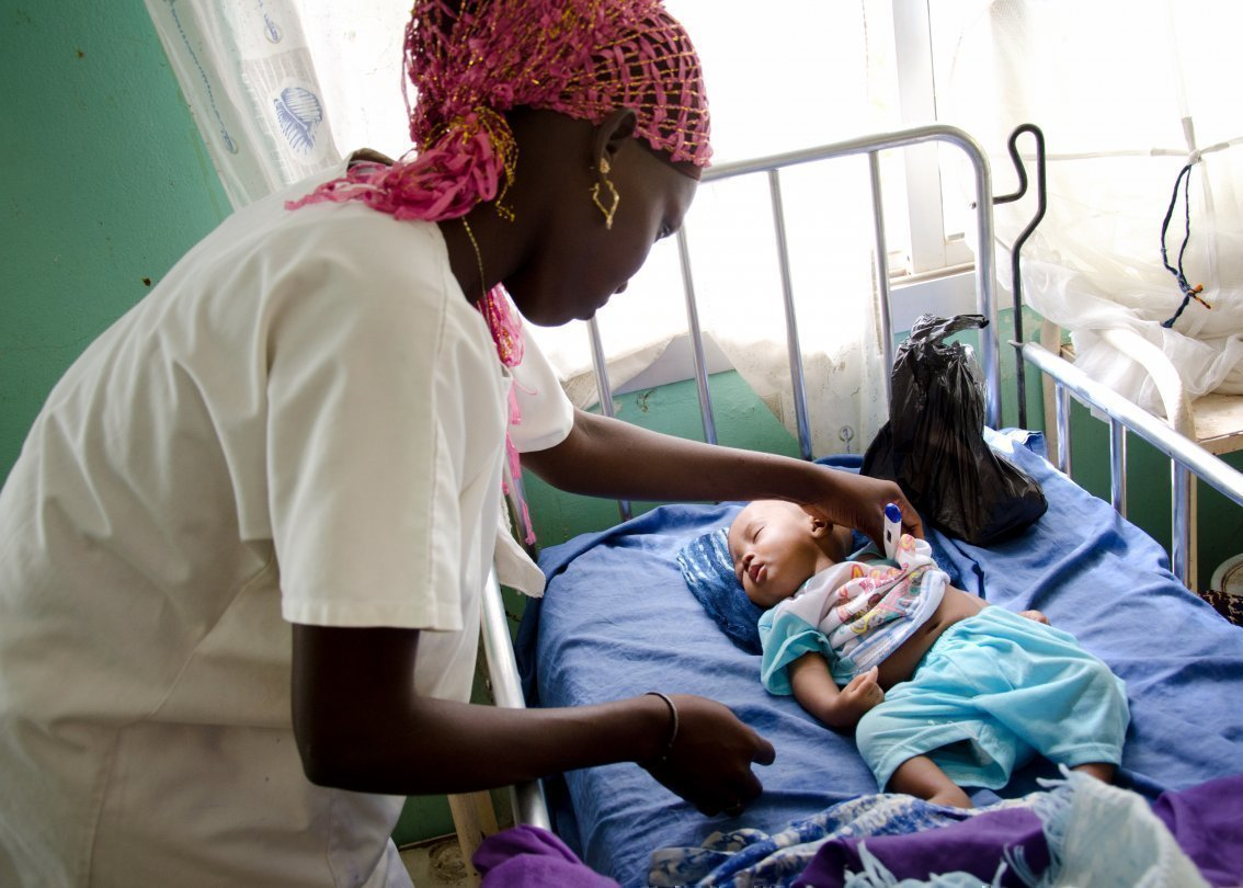 Une femme médecin avec un enfant africain dans un centre médical SOS.