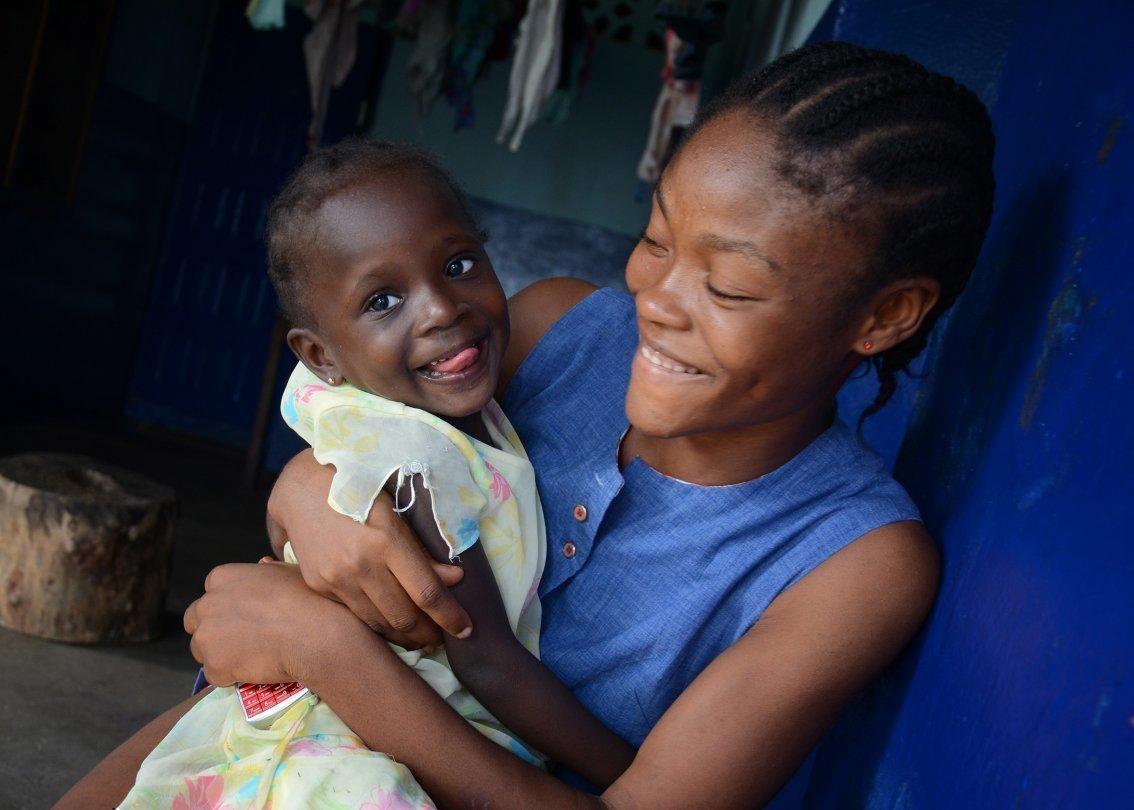 Une mère africaine d'un village d'enfants SOS avec un enfant qui rit dans ses bras.